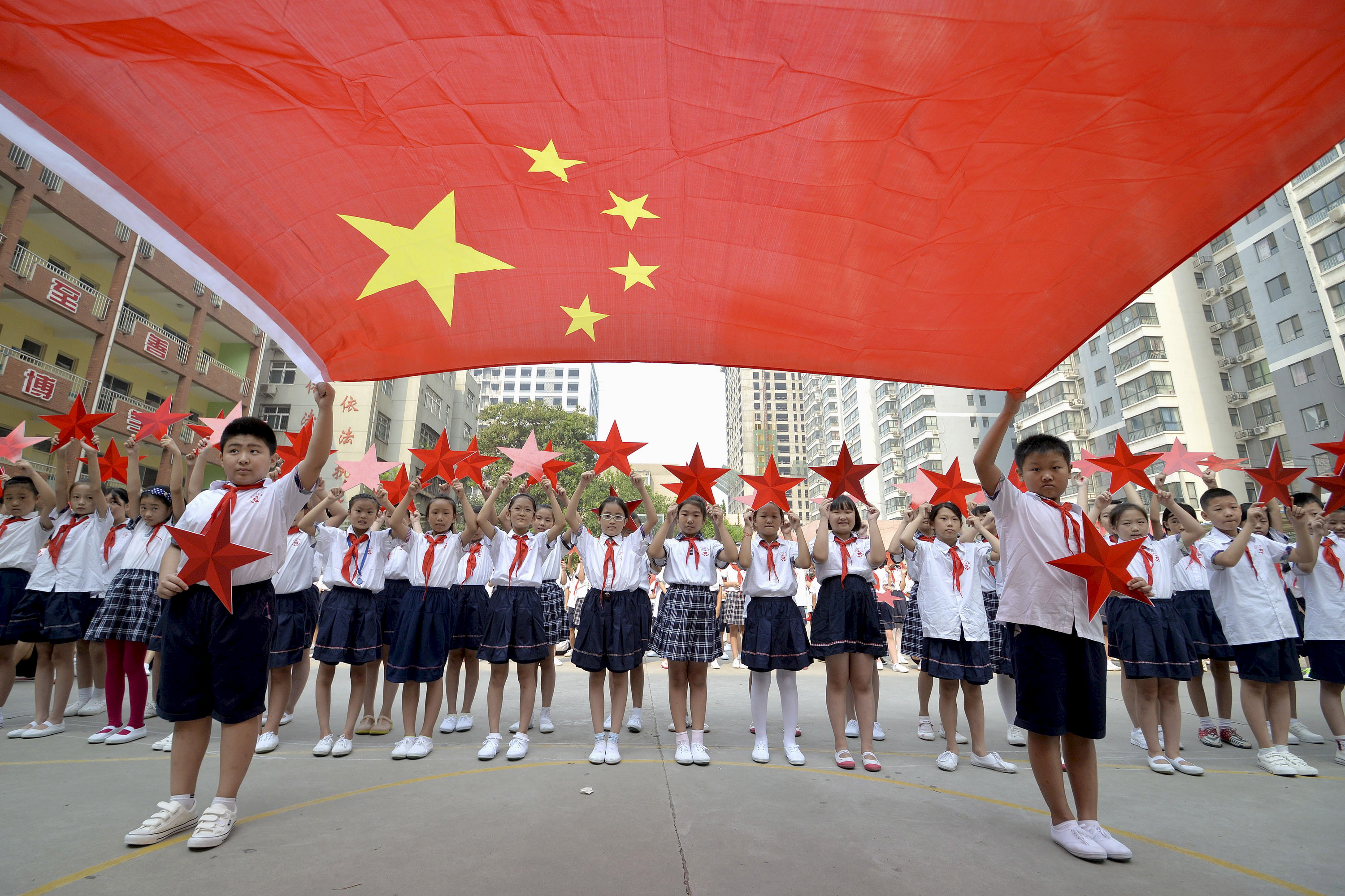 Students pose with a Chinese national flag and red stars during an event to mark the 70th anniversary of Japan's World War II surrender at a primary school in Handan, Hebei province, China, on Aug. 31, 2015