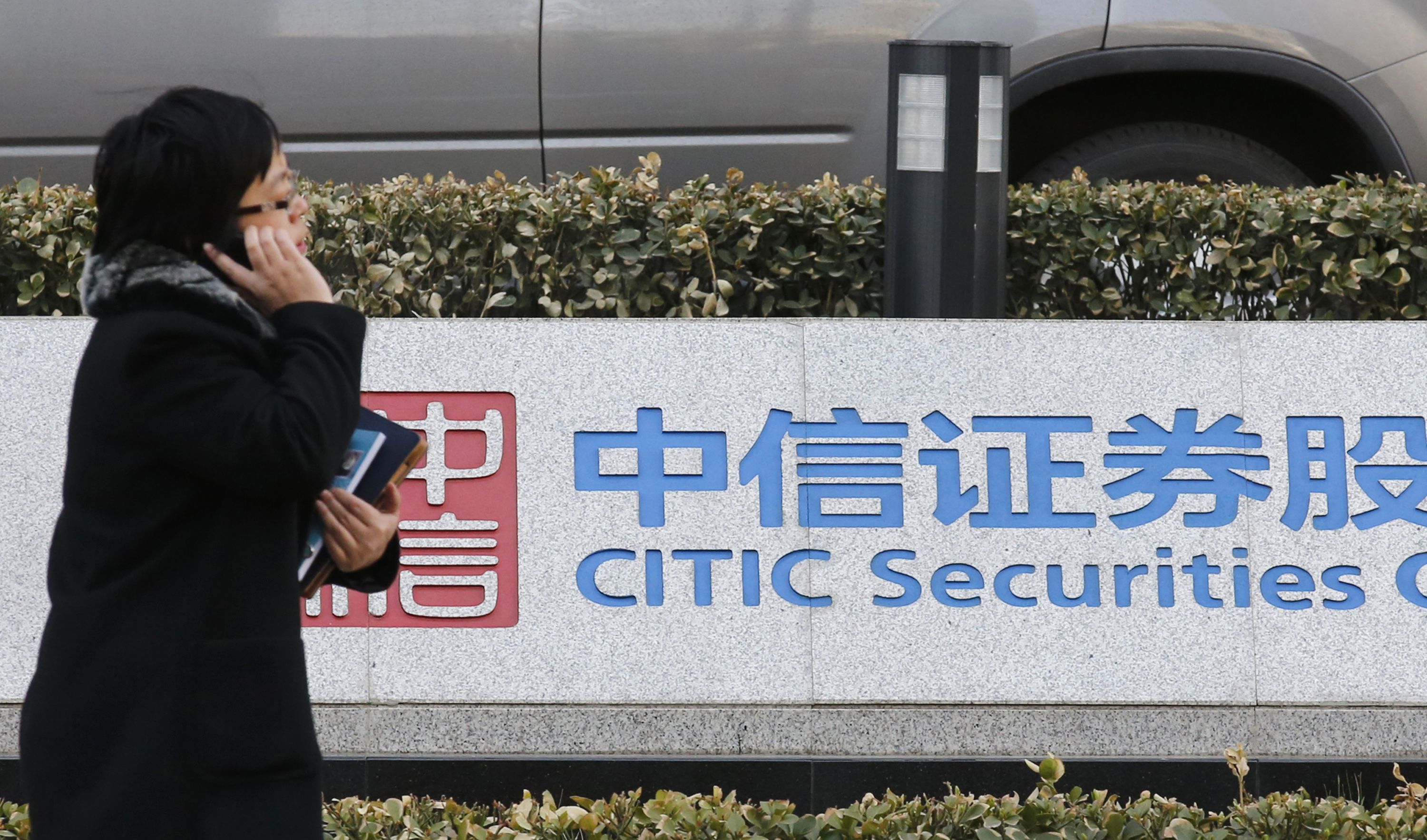 A woman walks past a signboard of CITIC Securities at its head office in Beijing March 27, 2013.