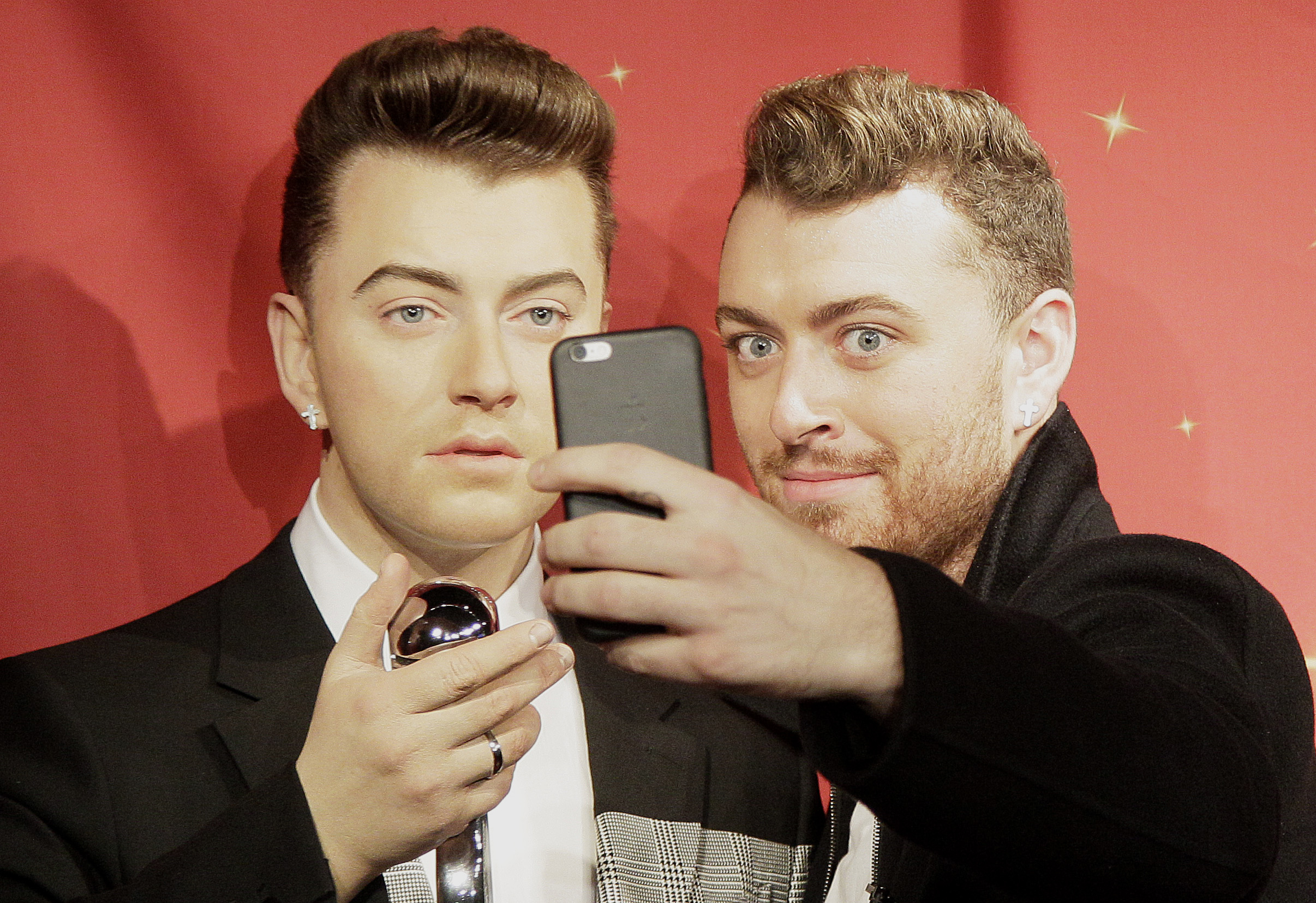 Singer Sam Smith takes a selfie next to his wax figure at Madame Tussauds wax museum in San Francisco on Aug. 10, 2015.