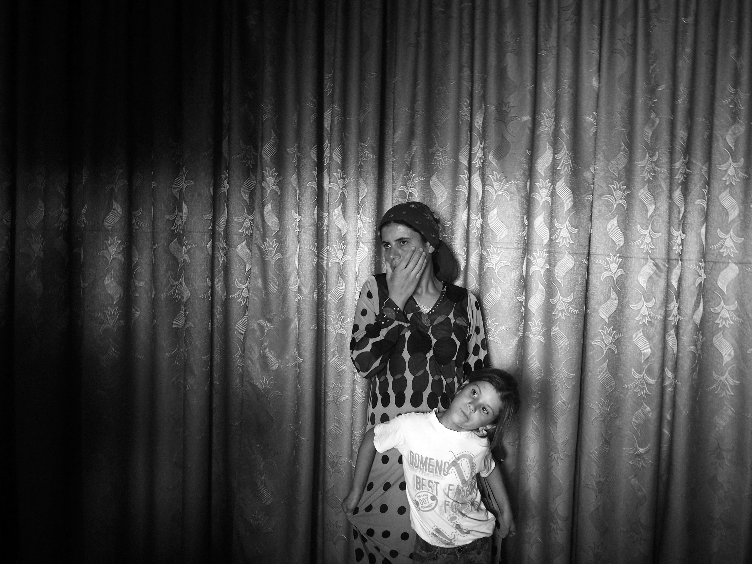 Shireen, 33, the widow of a YPG fighter, with her daughter, Astera, inside their home in Kobani. Kobani, Syria. Aug. 8, 2015.