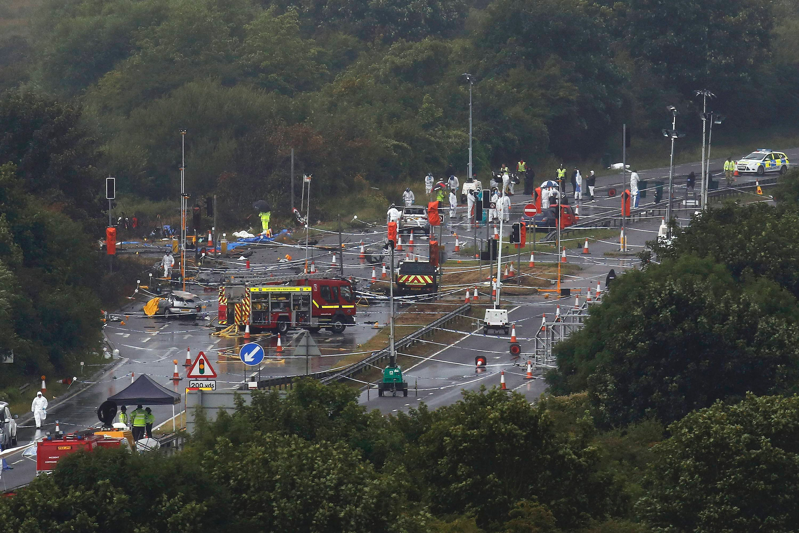 Emergency services and crash investigation officers continue to work at the site where a Hawker Hunter fighter jet crashed onto the A27 road at Shoreham near Brighton, U.K., Aug. 24, 2015.