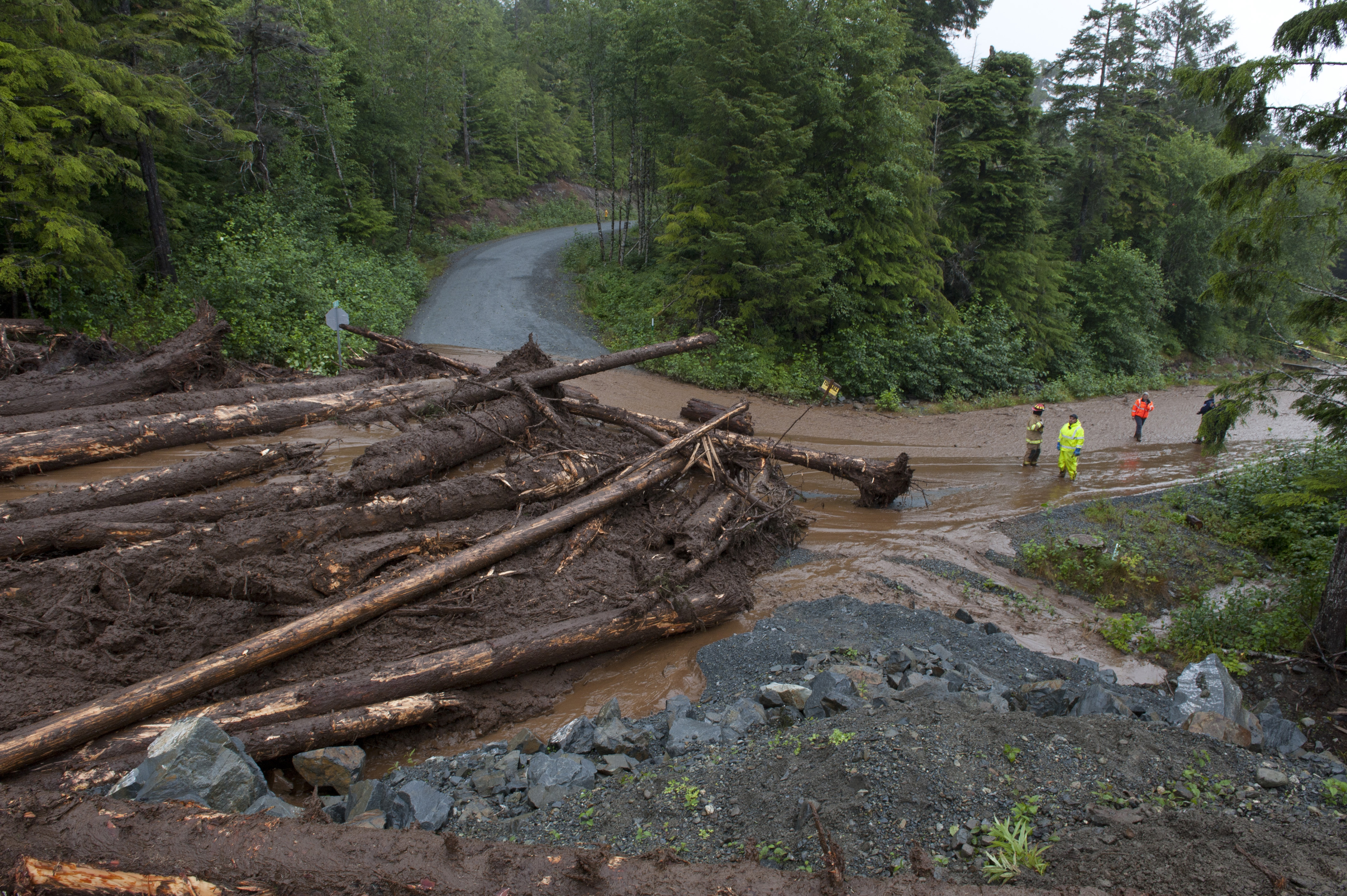 Construction workers and emergency crew members look at the damage caused by a landslide on Kramer Drive on Aug. 18, 2015, in Sitka, Alaska.