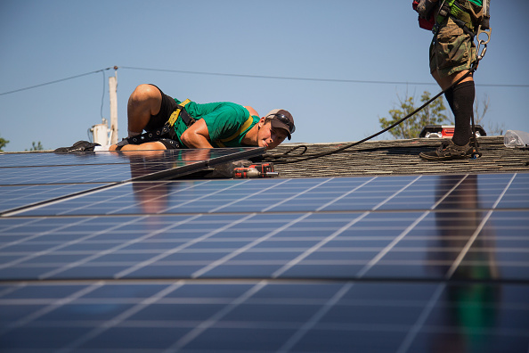 Dave Scarantino, senior installer for SolarCity Corp,   installs solar panels on the rooftop of a home in Kendall Park, N.J., U.S., on Tuesday, July 28, 2014.