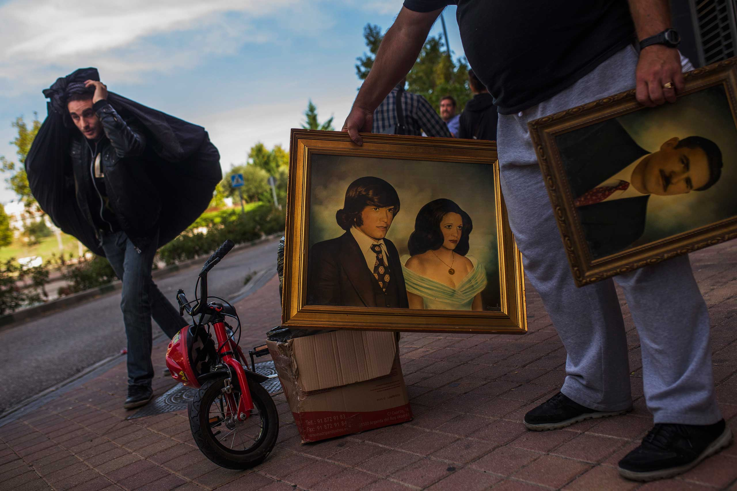 Friends and activists carry pictures and bags as they help Veronica Labradas to move out after the police evicted her family in Madrid. Oct. 2014.