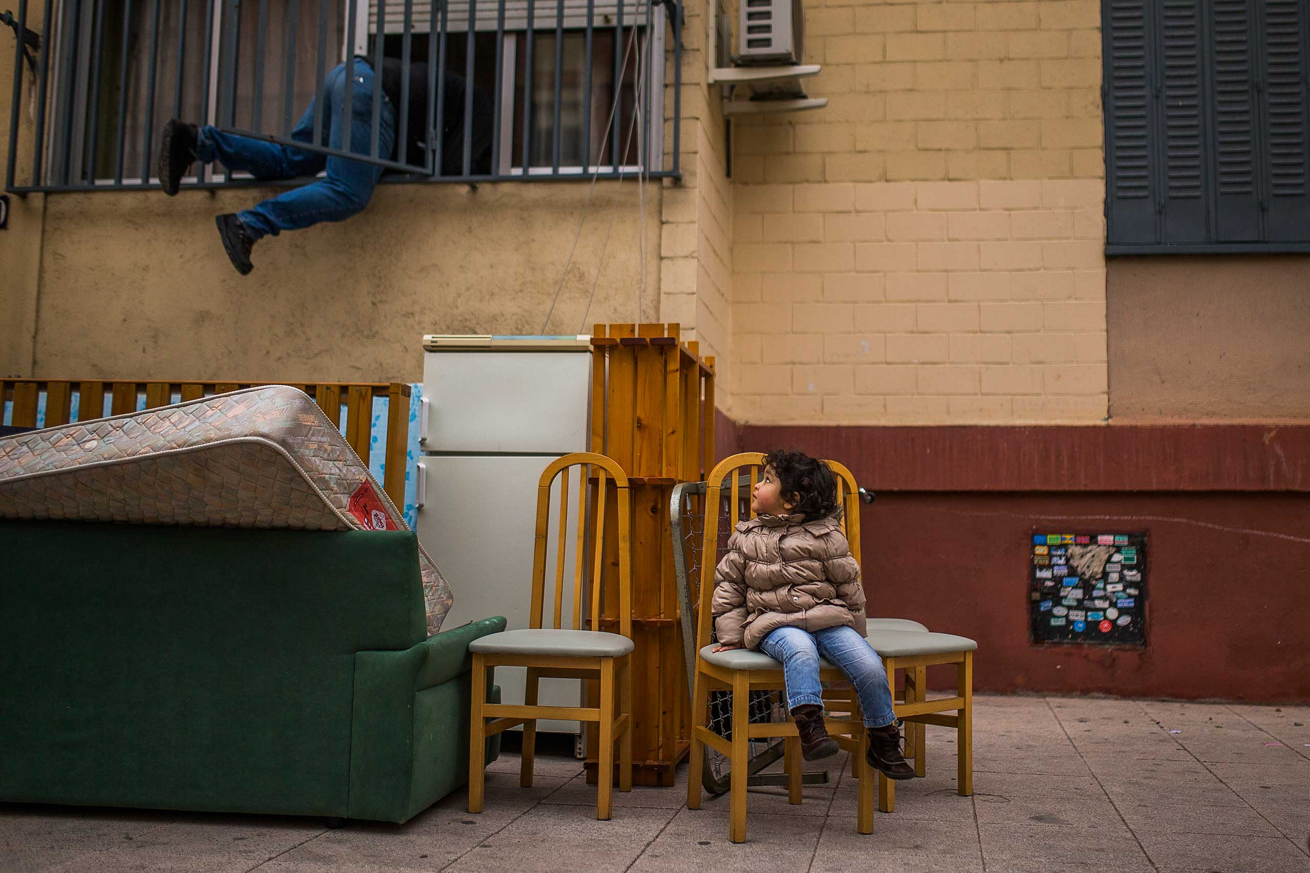 Diana Sofia Meliton, 2, watches a housing rights activist re-open her family's apartment after they were evicted, in Madrid. Feb. 2015.