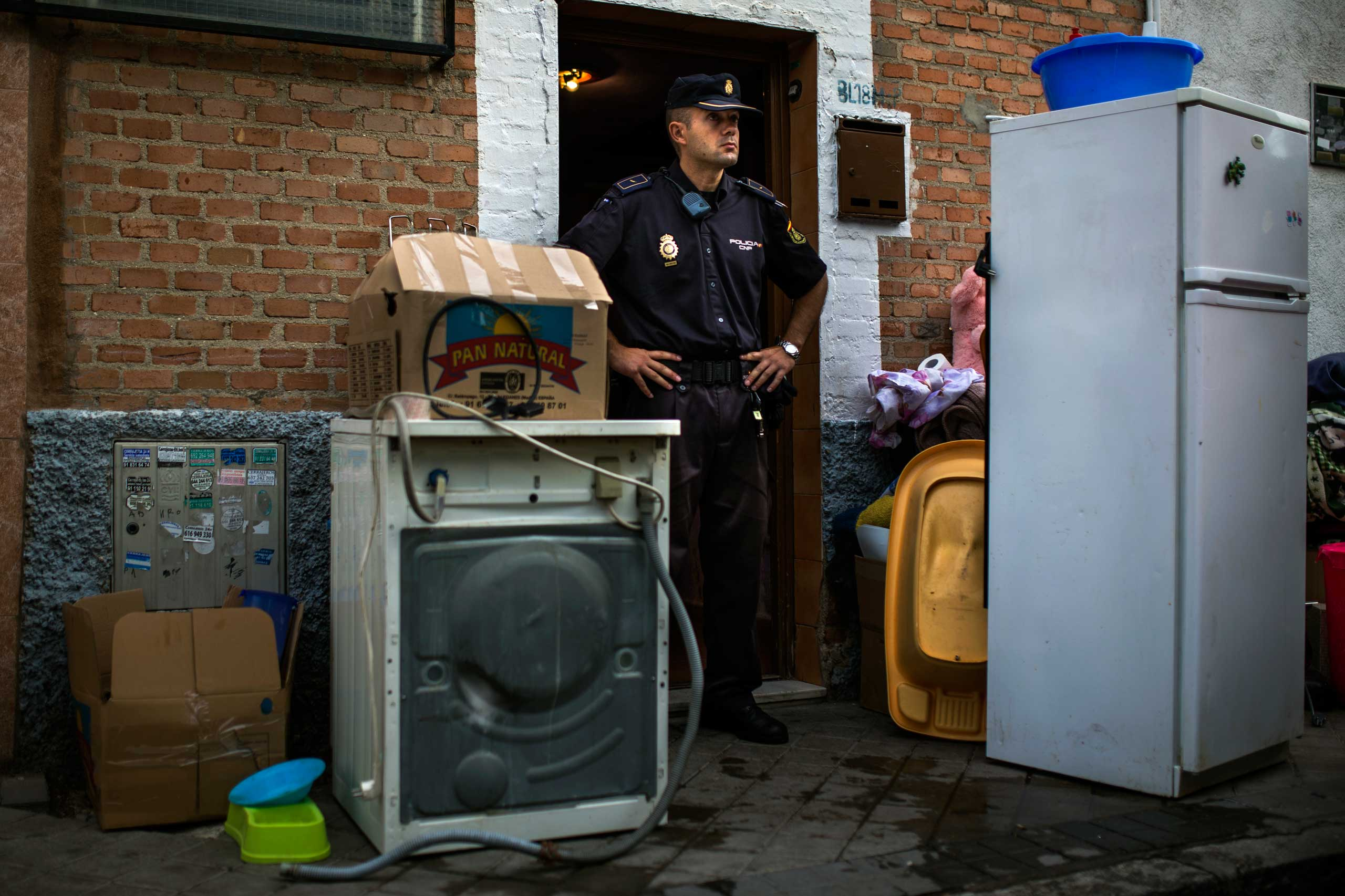 Police block the apartment's entrance  as Amalio Barrul Gimenez's belongings lay on the street after his family got evicted in Madrid. June 2014.