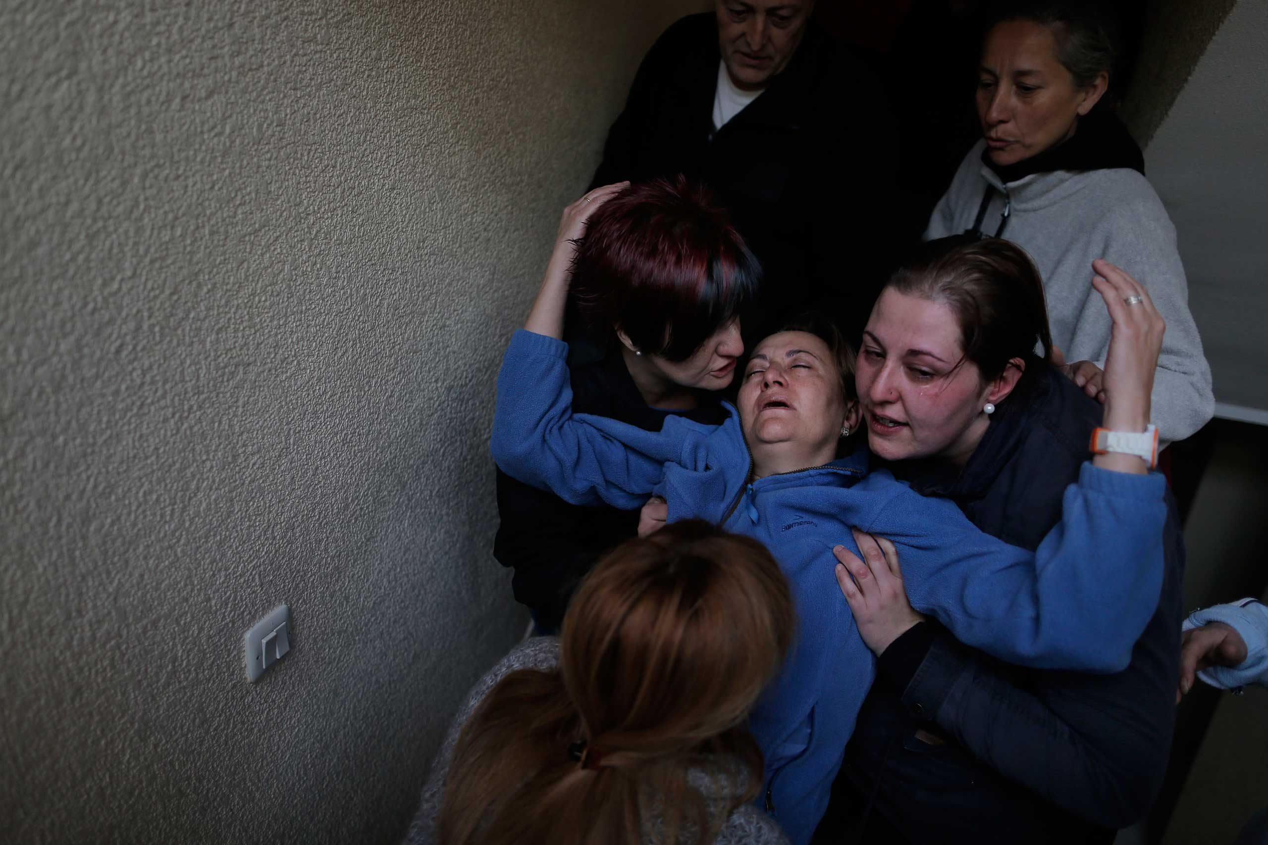 Soledad Carrasquilla Delgado, 53, center, gets help from her family and  members of the Victims' Mortgage Platform, as she faints during a panic attack following the postponement of her family's eviction in Madrid. Oct. 2013.