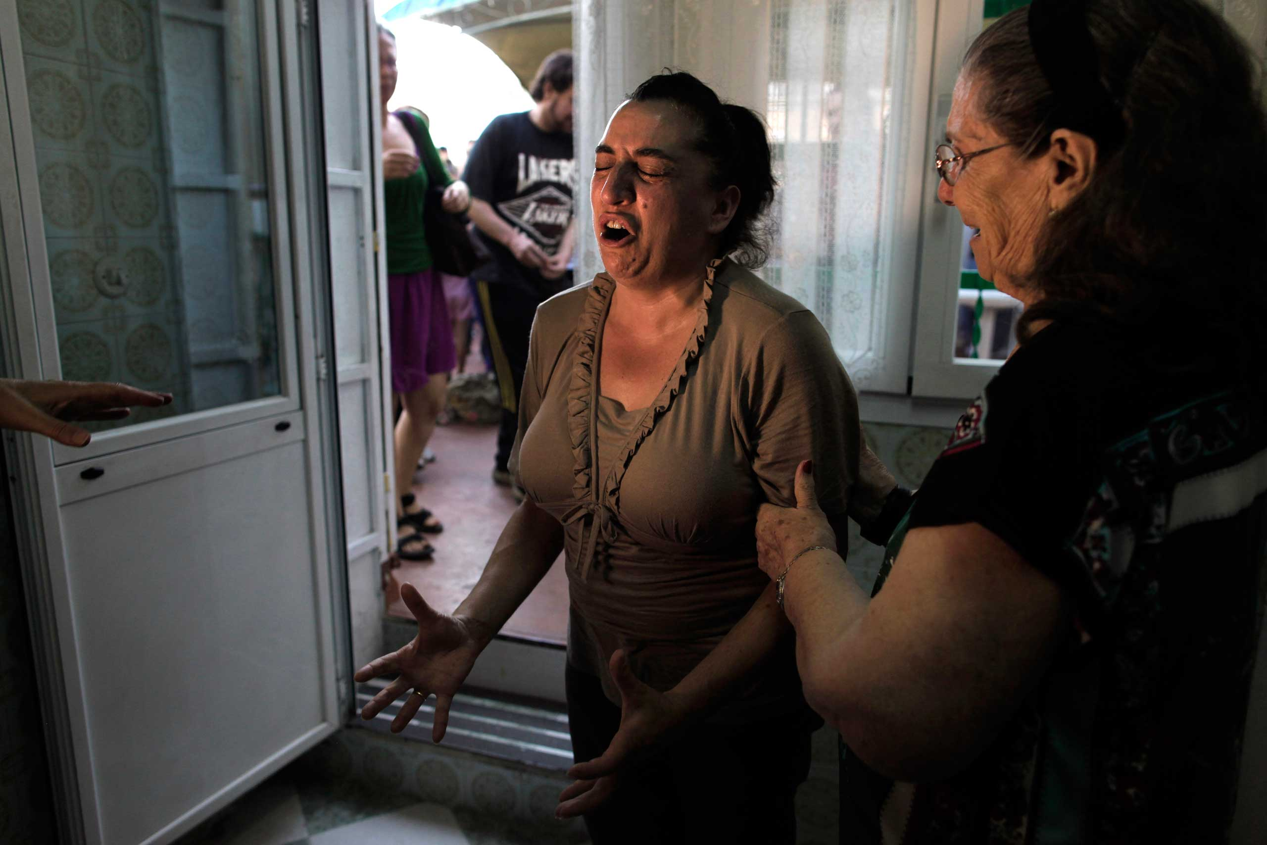 Luisa Gracia Gonzalez, 44, cries as her family's eviction and the demolition of her house by a forced expropriation was postponed in Madrid.  Aug. 2013.