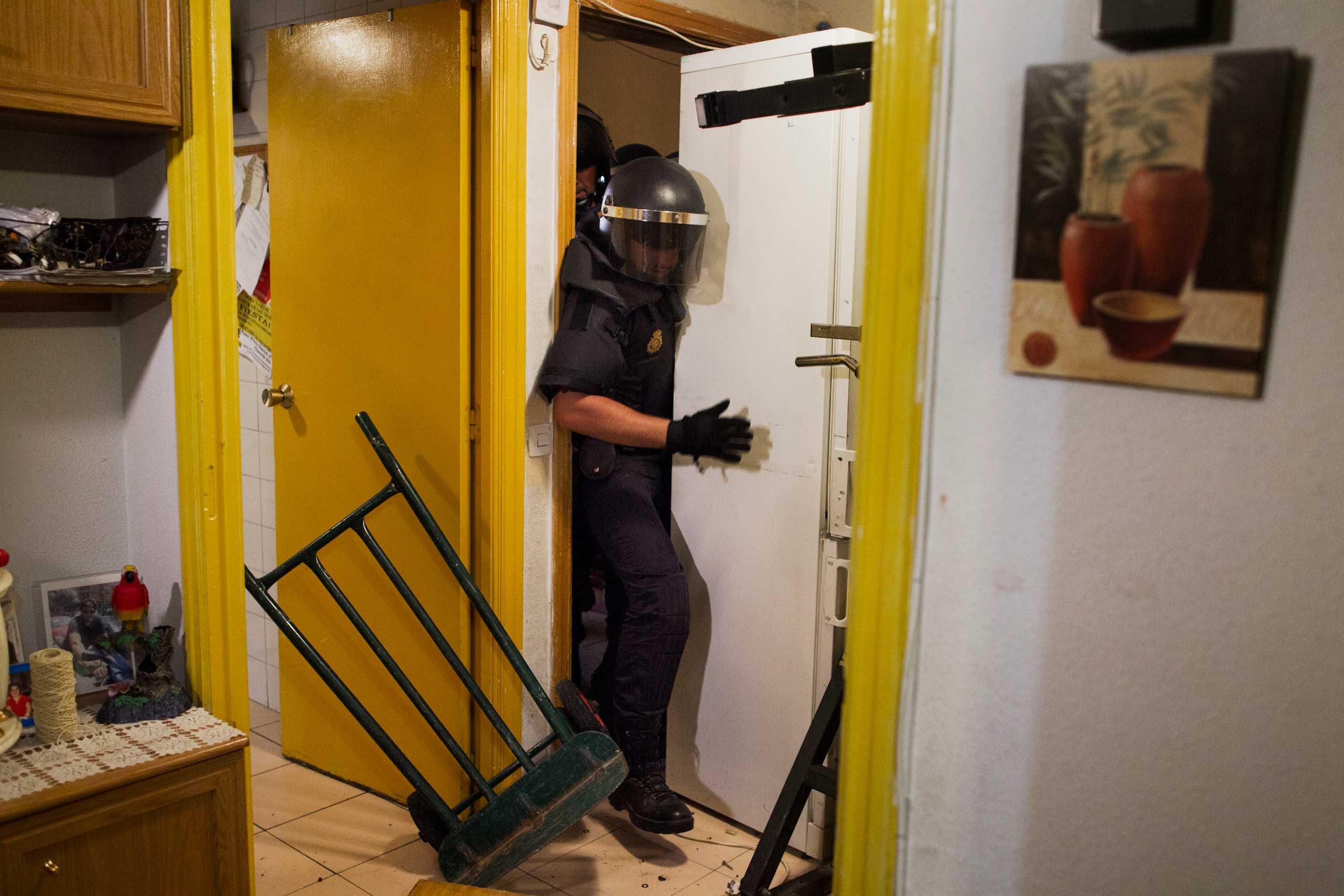 Police break into Maria Isabel Rodriguez Romero's apartment  to evict her family in Madrid. Sept. 2013.