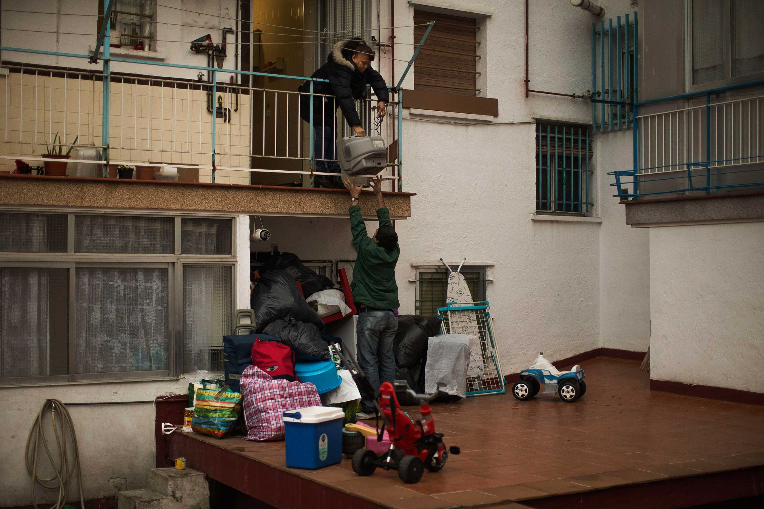 Mercedes Pincay, 50, empties her apartment through the back door during her eviction in Madrid. Dec. 2014.