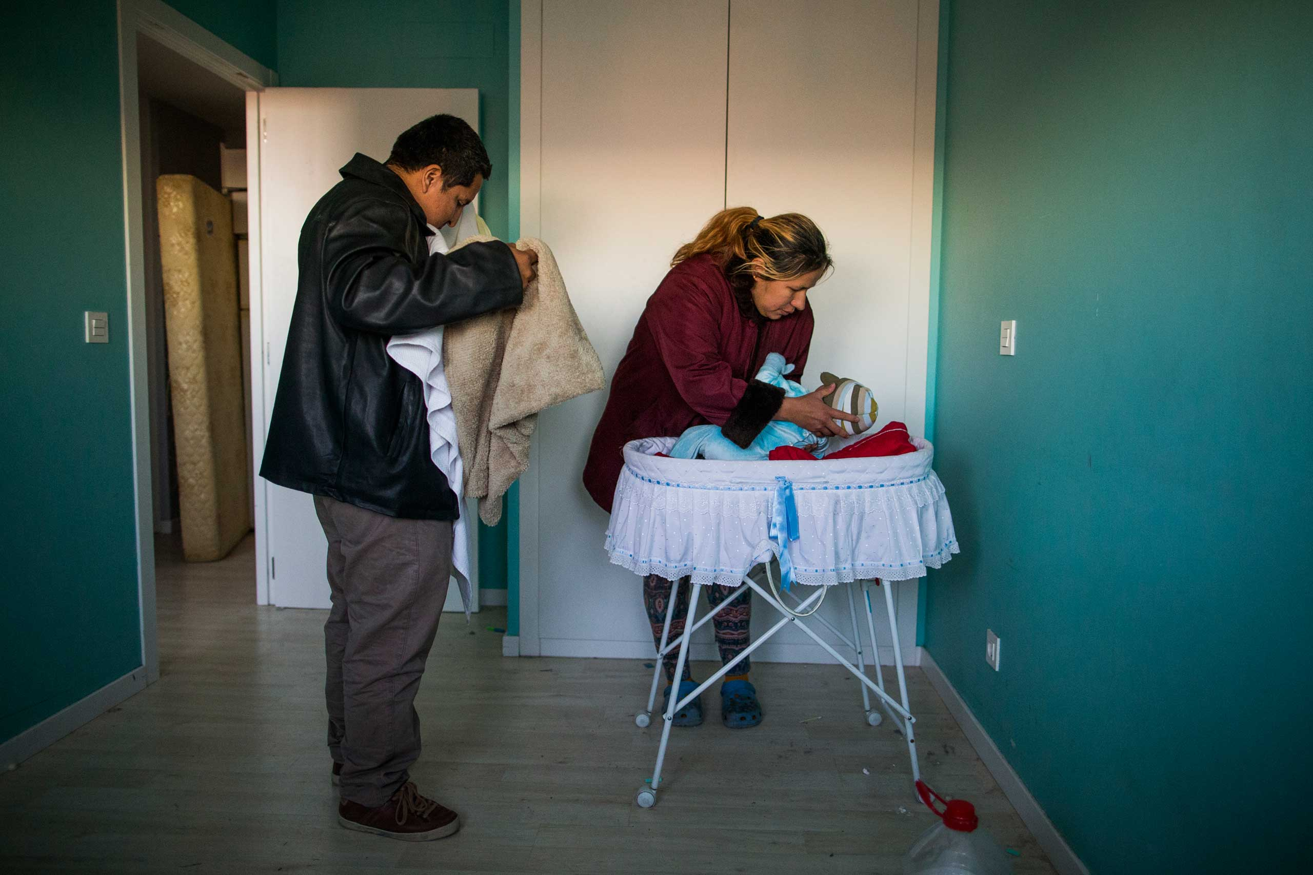 Furniture is packed behind the main door to stop riot police from entering the apartment as Cecilia Paredes and her husband Wilson Ruilova prepare to leave with their baby Dilan during their eviction in Madrid. Jan. 2015.