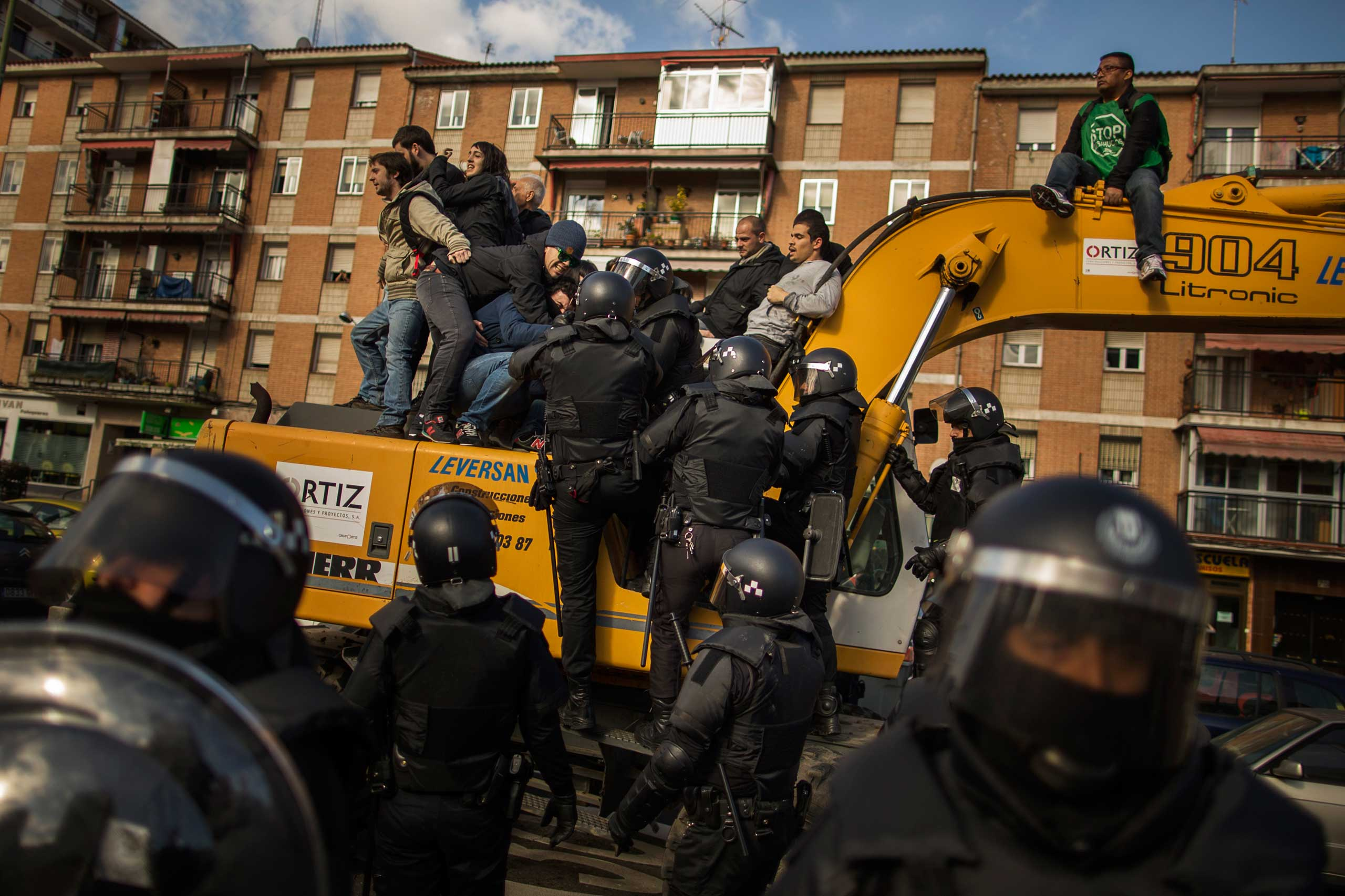 Riot Police remove housing rights activists who climbed on an excavator in an effort to stop Luisa Gracia Gonzalez and her family's eviction and the demolition of their house by a forced expropriation in Madrid. Feb. 2015.