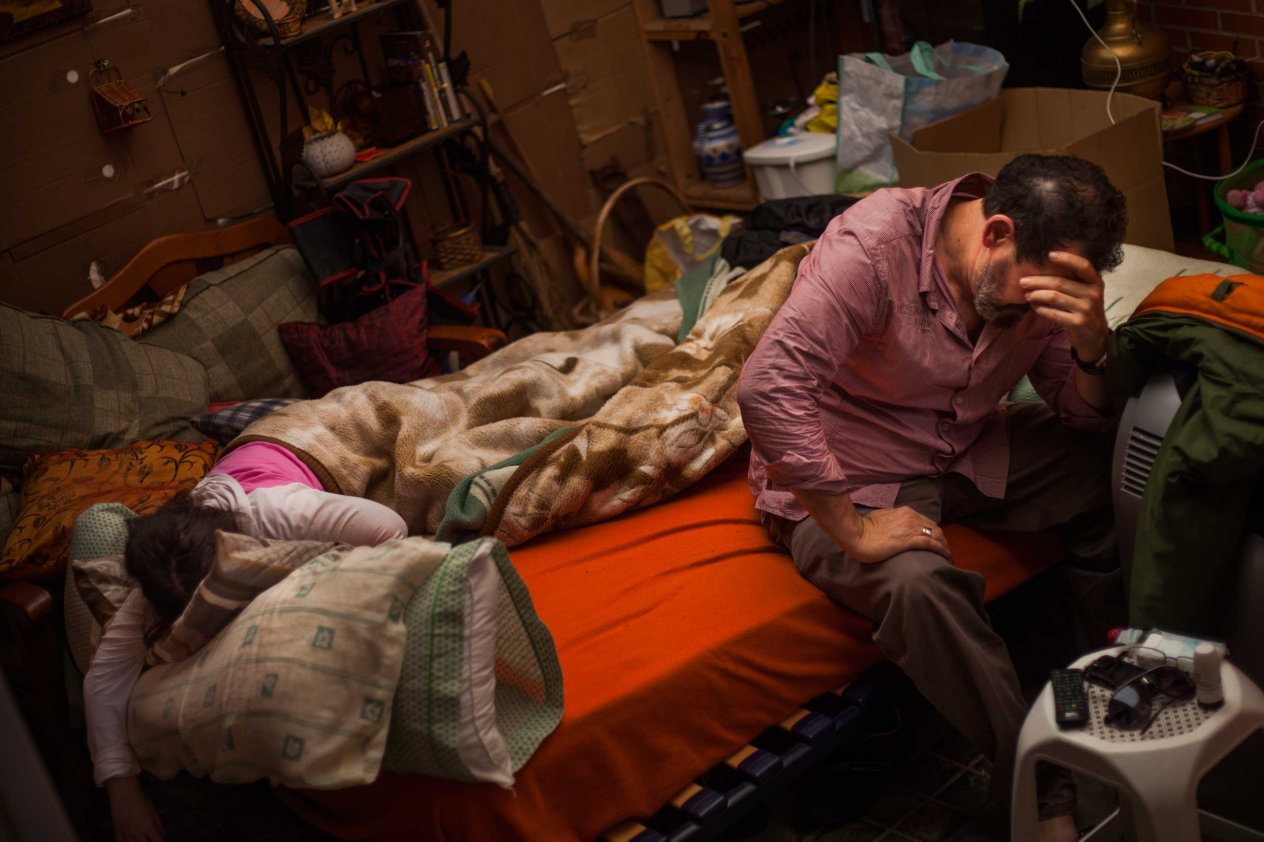 Benigno Ferrer, 59, gestures beside his daughter Maria Isabel Ferrer Rodriguez, 8, as they wake up outside the apartment from which they got evicted in Madrid. Oct. 2013.