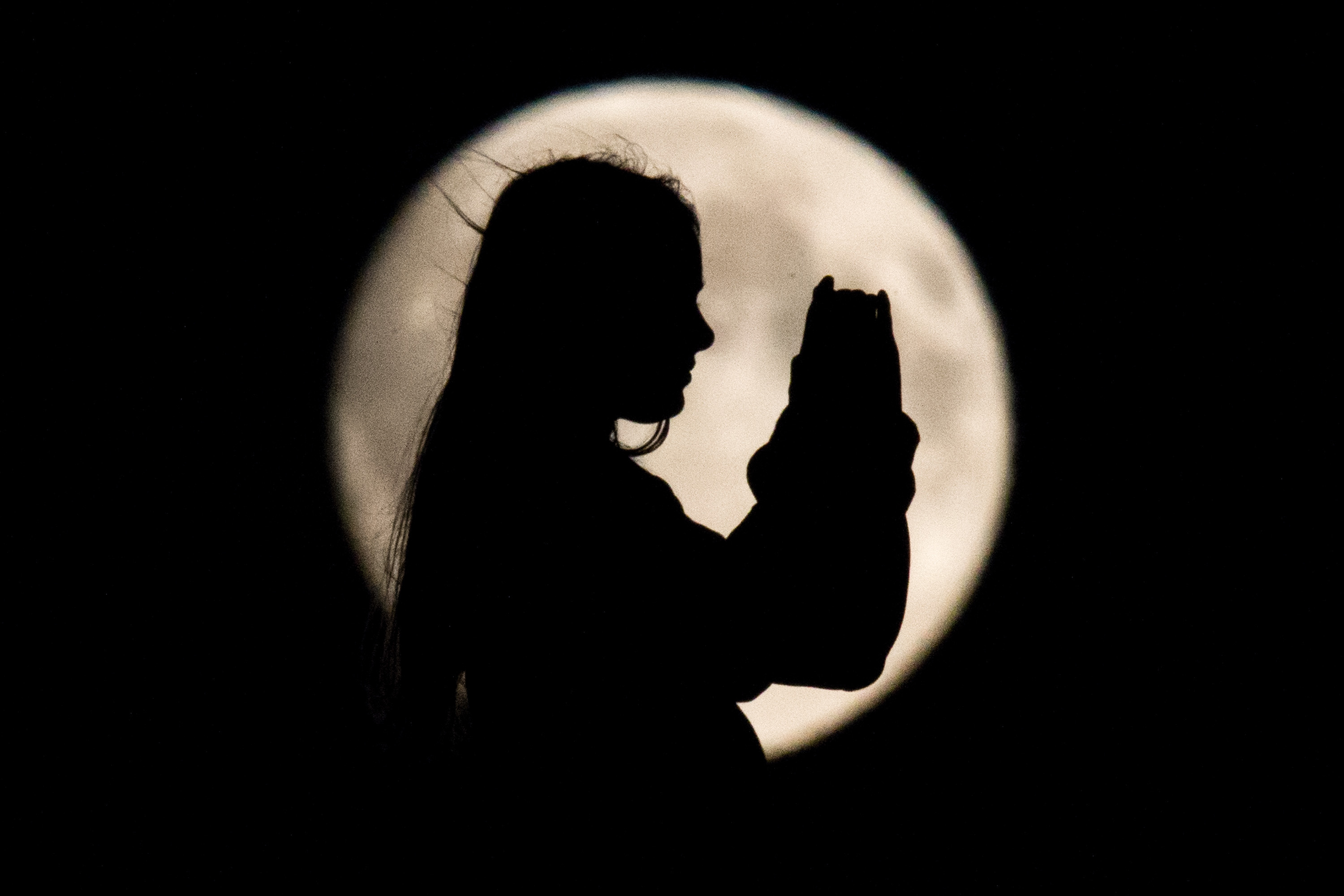The silhouette of a girl appears as against the backdrop of of a bright moon in Hanover, Germany on Aug. 29, 2015.