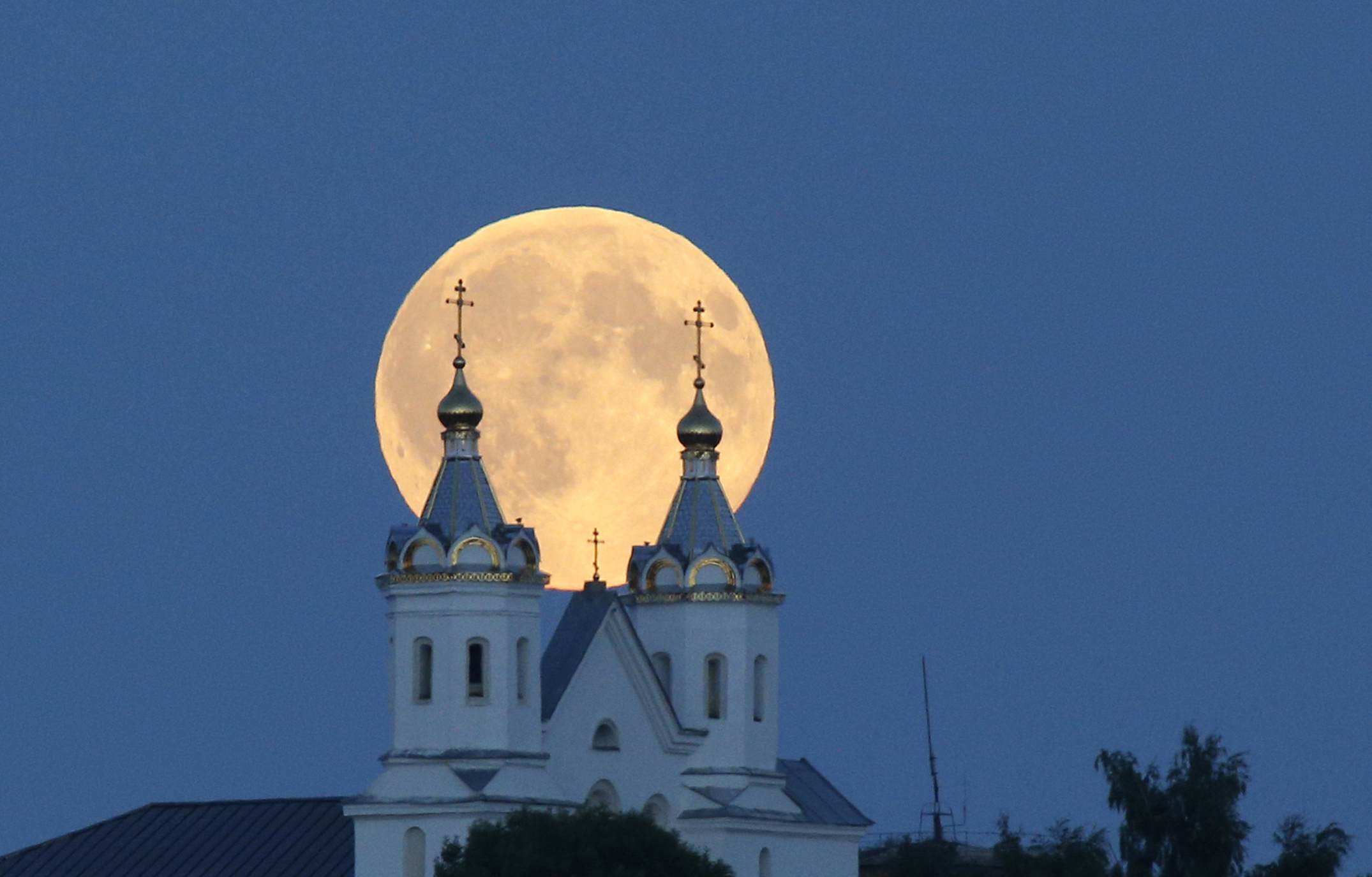 A perigee moon, also known as a super moon, rises above the Orthodox Church in the town of Novogrudok, Belarus on Aug. 29, 2015.
