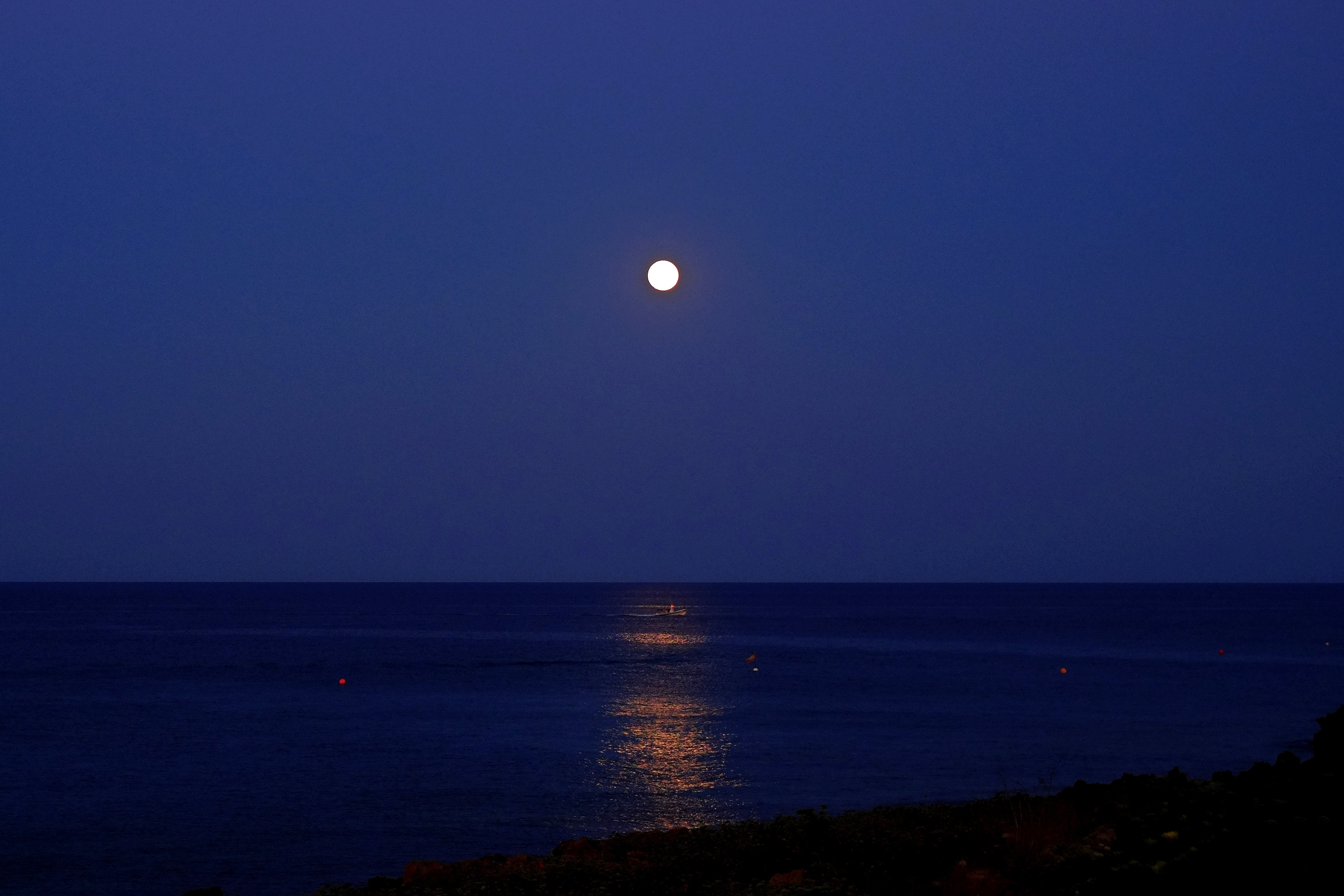 A boat on the sea passes under the light of the full moon at Protaras resort in the southeast part of the island of Cyprus on Aug. 29, 2015.