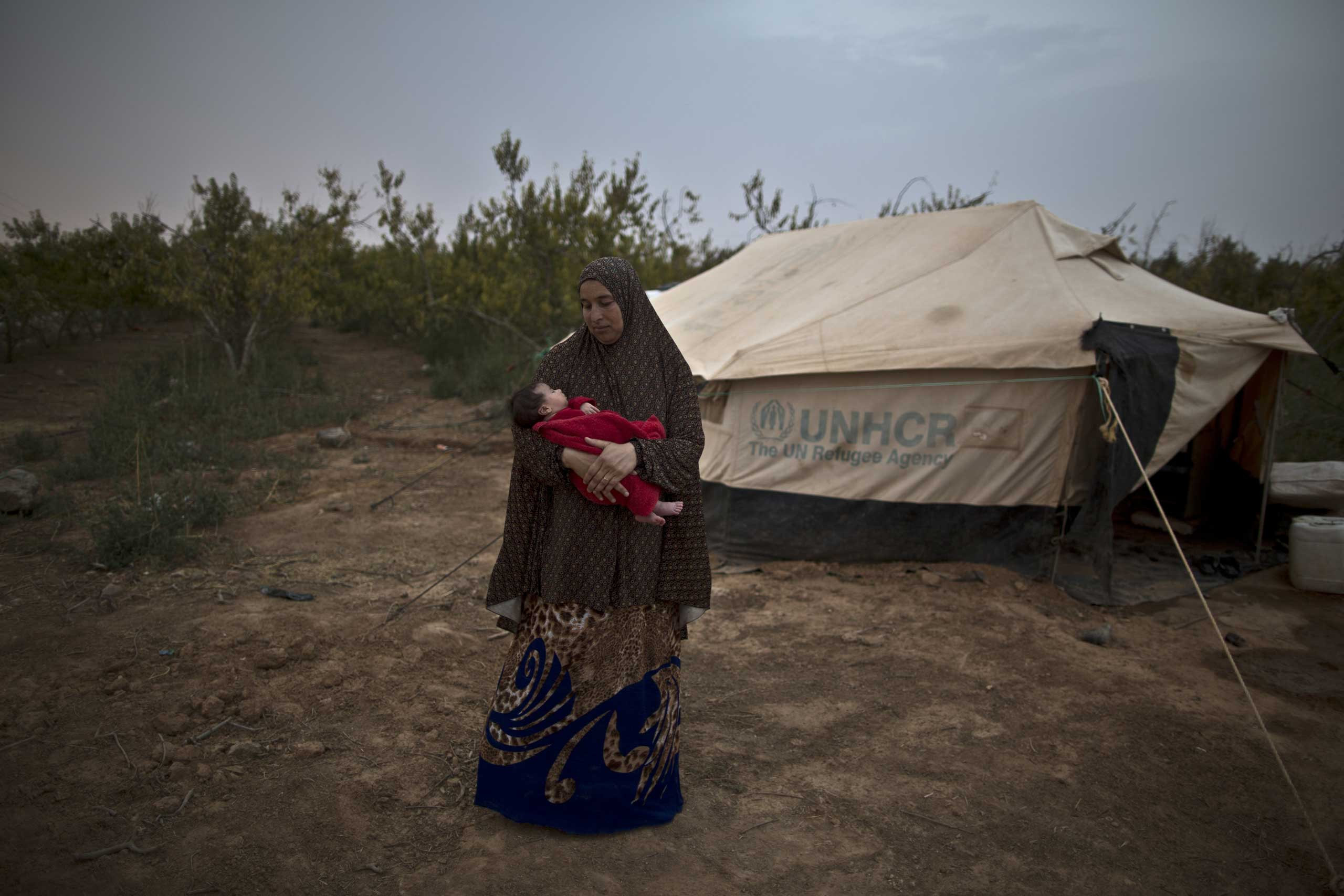 We are left alone. No one comes to check on us. We live by the roadside.   Mona Hussein, 33, holds her month-old daughter Zahra, on Aug. 4, 2015.