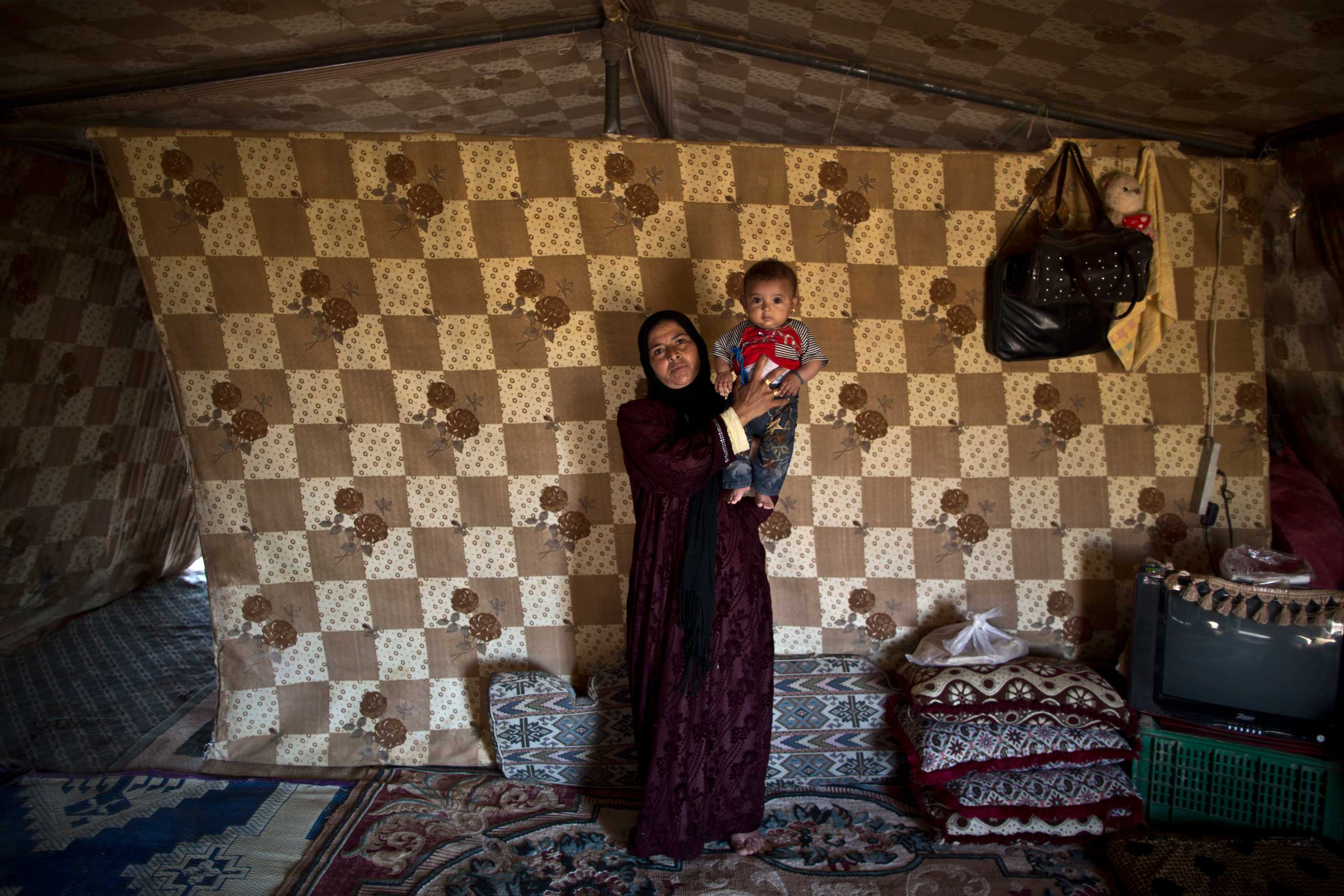 We are the ones who live outside of the registered camps with miserable conditions. My husband has no work. All we want is people to help us and pay us some attention.  Mahdiya Alkhalid, 36, holds her 18-week-old daughter Mariam, on Aug. 13, 2015.