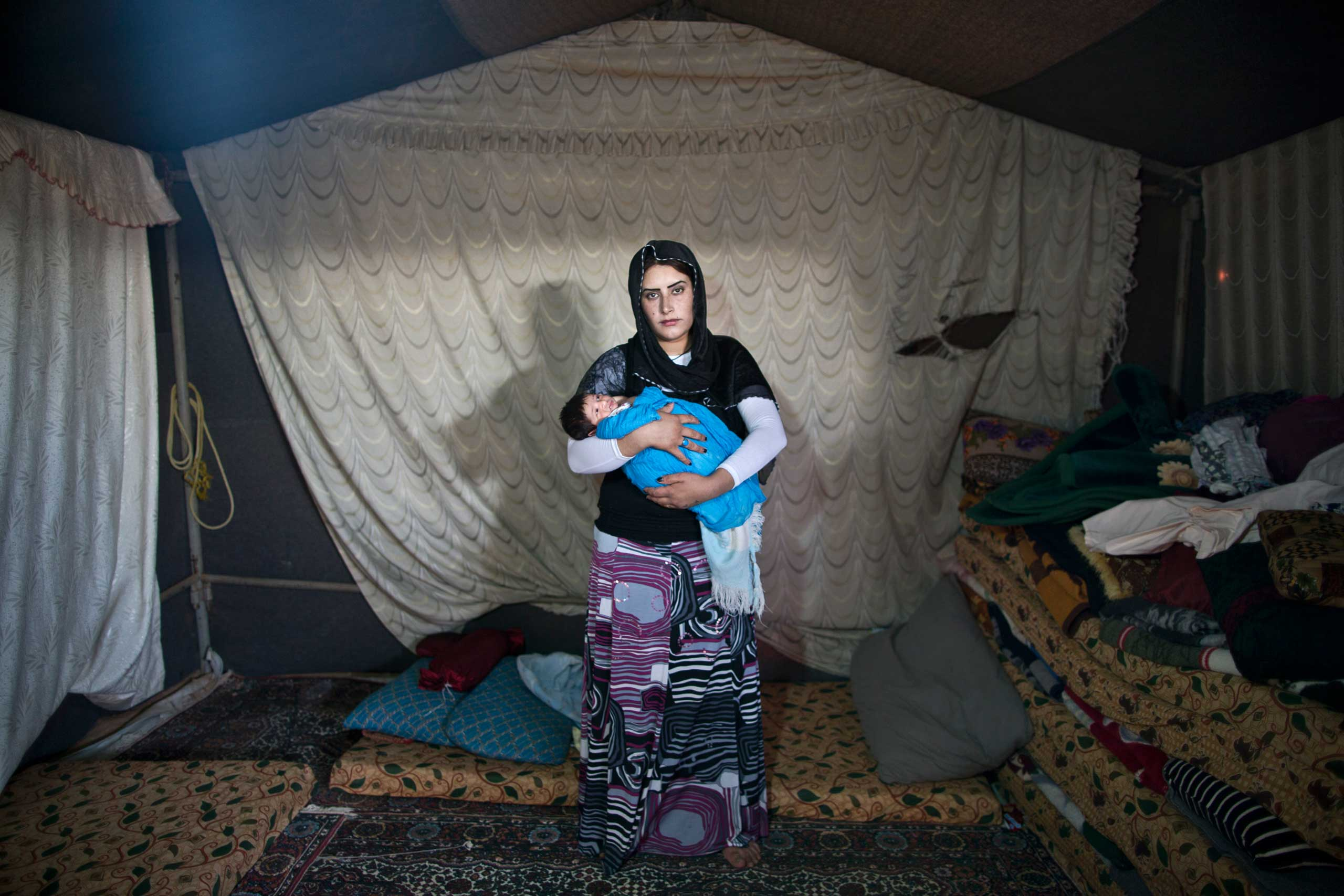 Winter is so cold, summer is hot and dry. My husband hardly works and some of the decisions we had to make have been deciding what is more important: To buy bread to feed ourselves or medicine in case my child is in need?  Syrian refugee Wadhah Hamada, 22, holds her 10-day-old son Ra'fat inside her father's tent near the Syrian border, on the outskirts of Mafraq, Jordan, on Aug. 11, 2015.