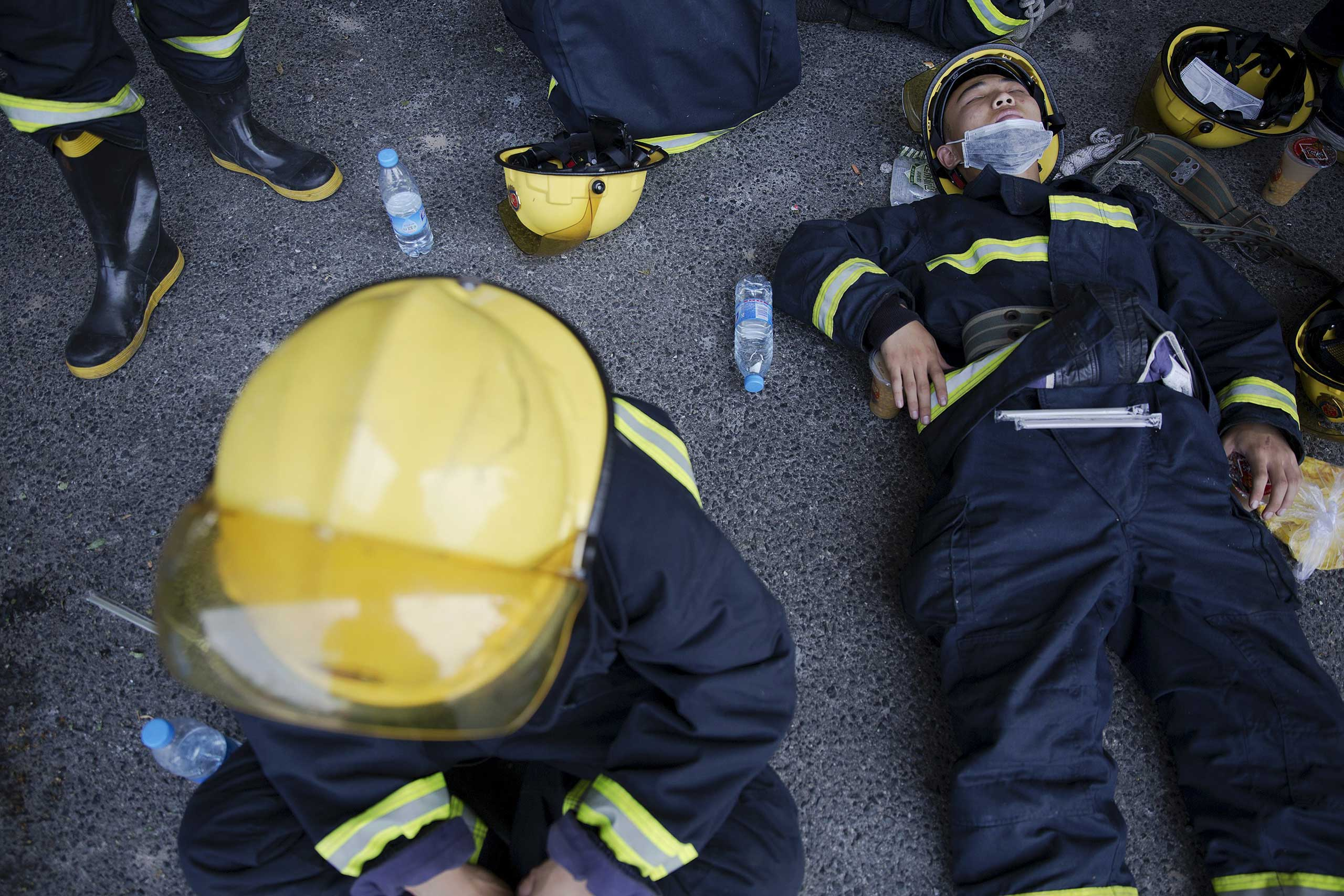 Firefighters take a break after trying to put fire down at the explosion site in Binhai new district in Tianjin, China, on Aug. 13, 2015.