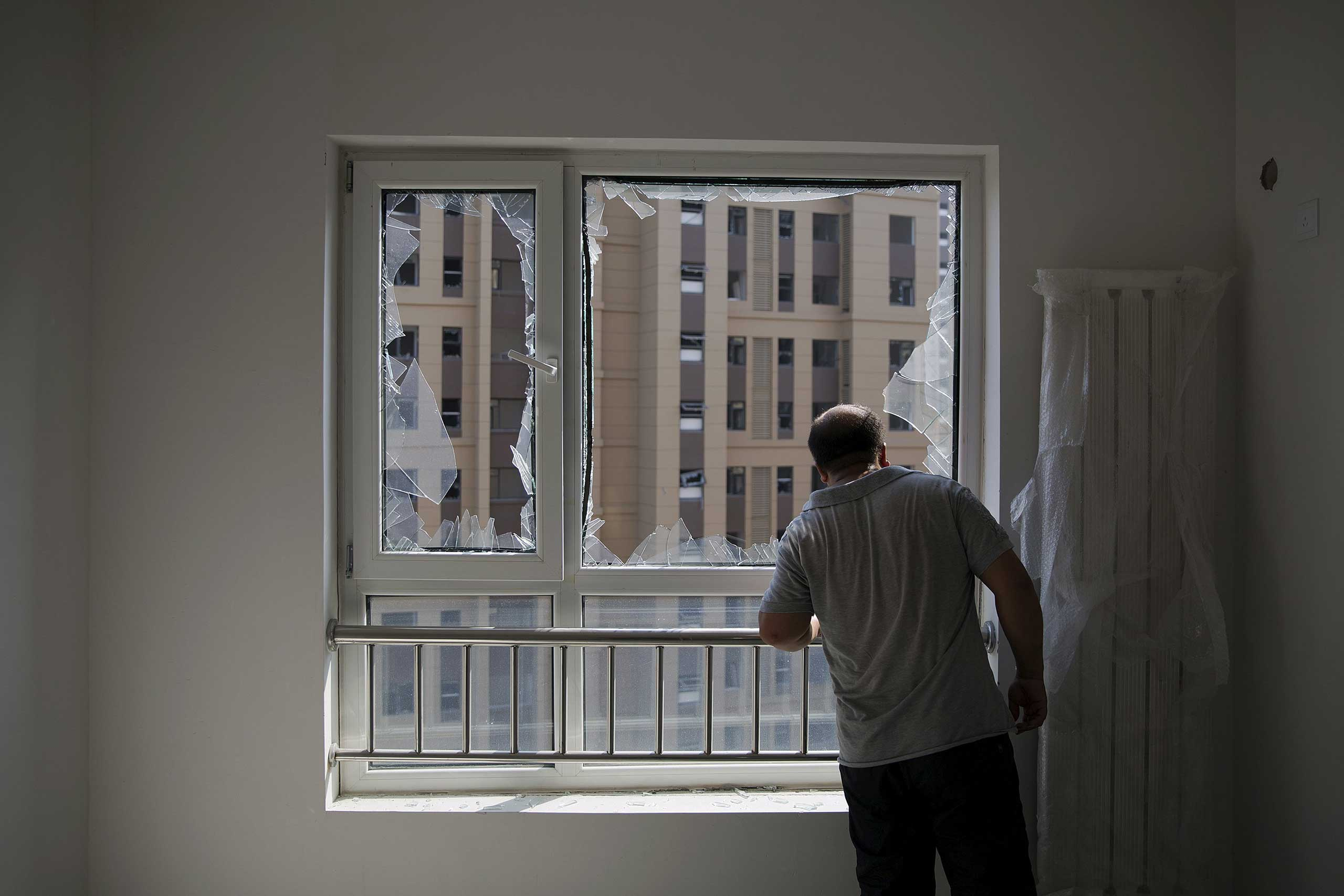 A man looks out from inside a damaged residential building near the site of the explosions at the Binhai new district, Tianjin, on Aug. 13, 2015.