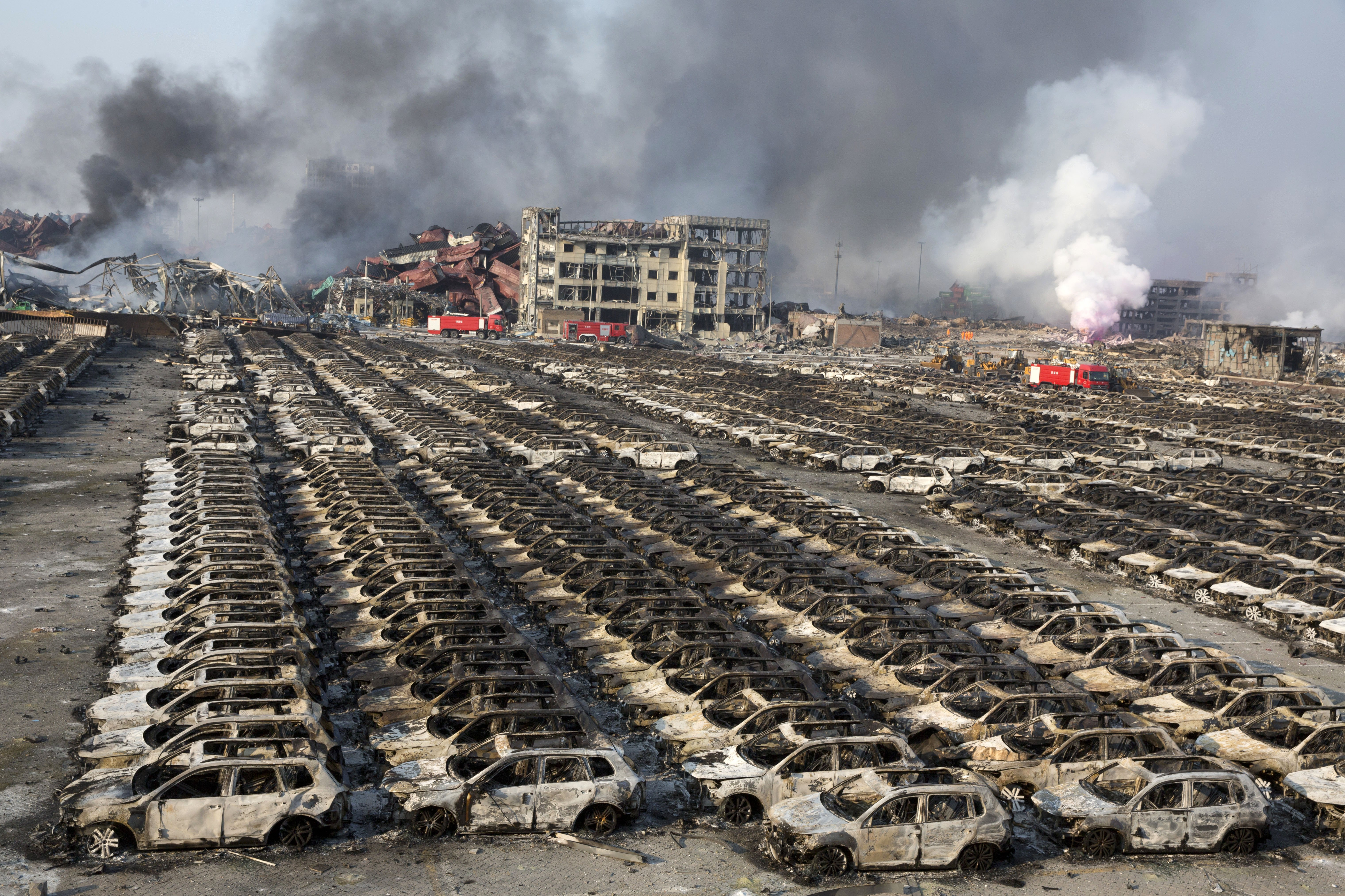 Smoke billows from the site of an explosion that reduced a parking lot filled with new cars to charred remains at a warehouse in northeastern China's Tianjin municipality on Aug. 13, 2015.