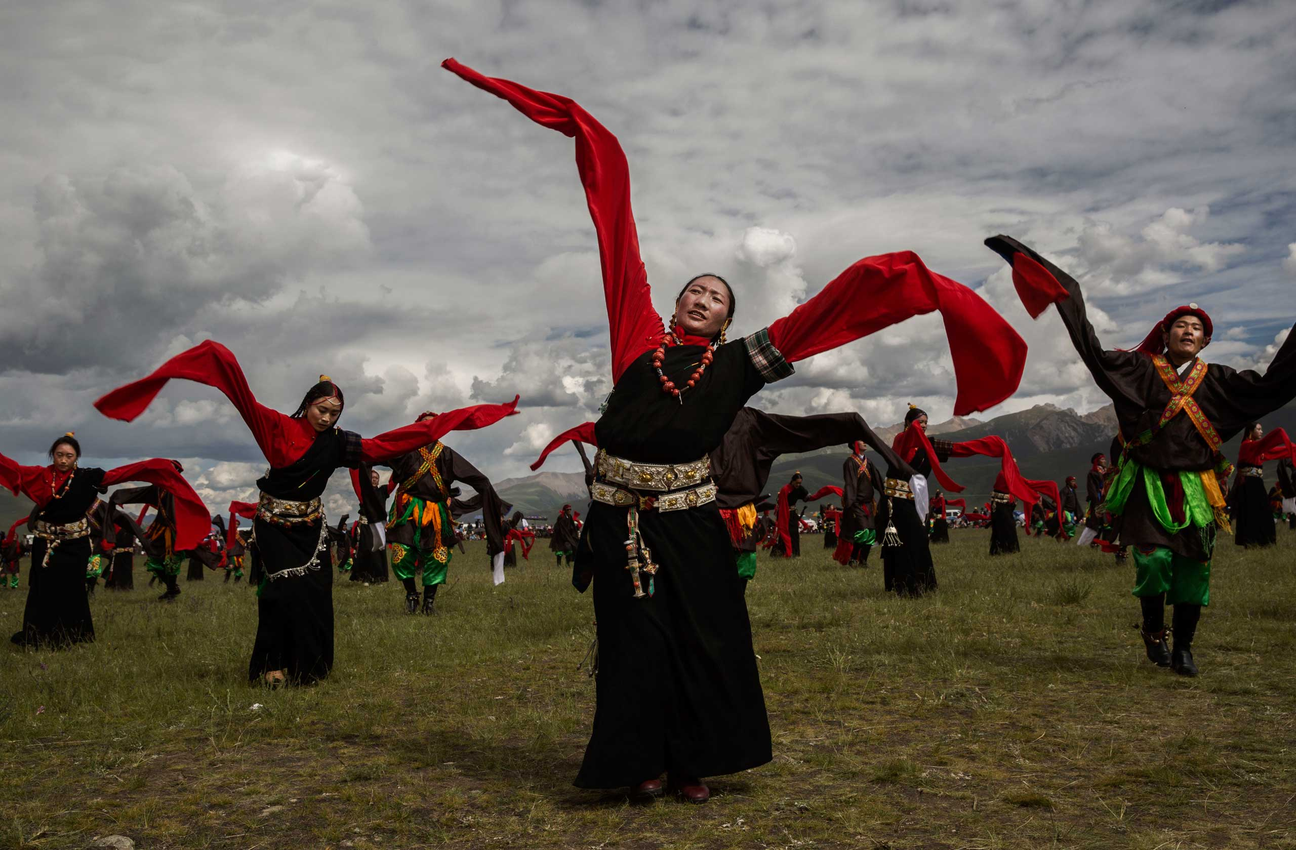 Ethnic Tibetans wearing traditional costume dance  at a local government sponsored festival on the Tibetan Plateau in Yushu County on July 25, 2015.
