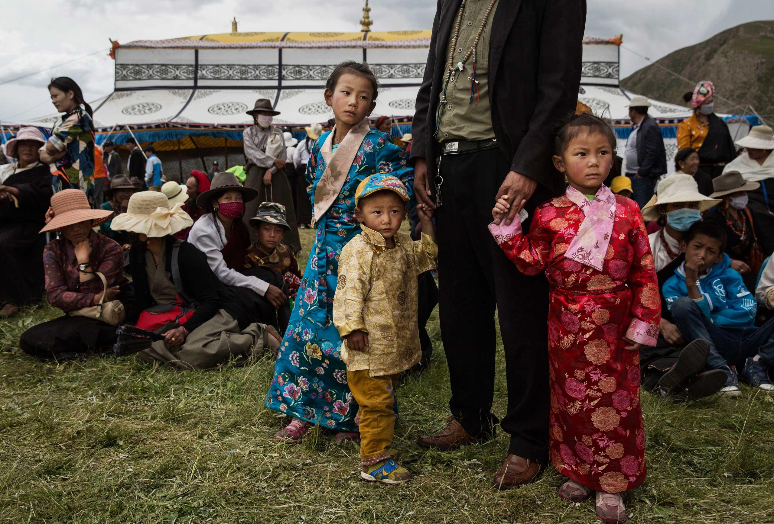 Ethnic Tibetan nomad children wear fancy dress as they watch a horse festival on the Tibetan Plateau in Yushu County,  on July 26, 2015.