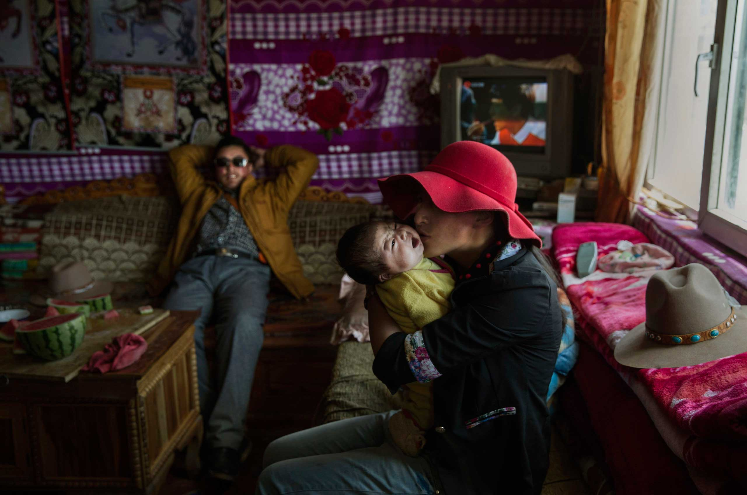 Former Tibetan nomad Kyipotsomo kisses her son Kunchok, 3 months, as father Jamyang Palden looks on as they sit in the living room of their house in a government resettlement community  on the Tibetan Plateau in Madou County, on July 23, 2015.