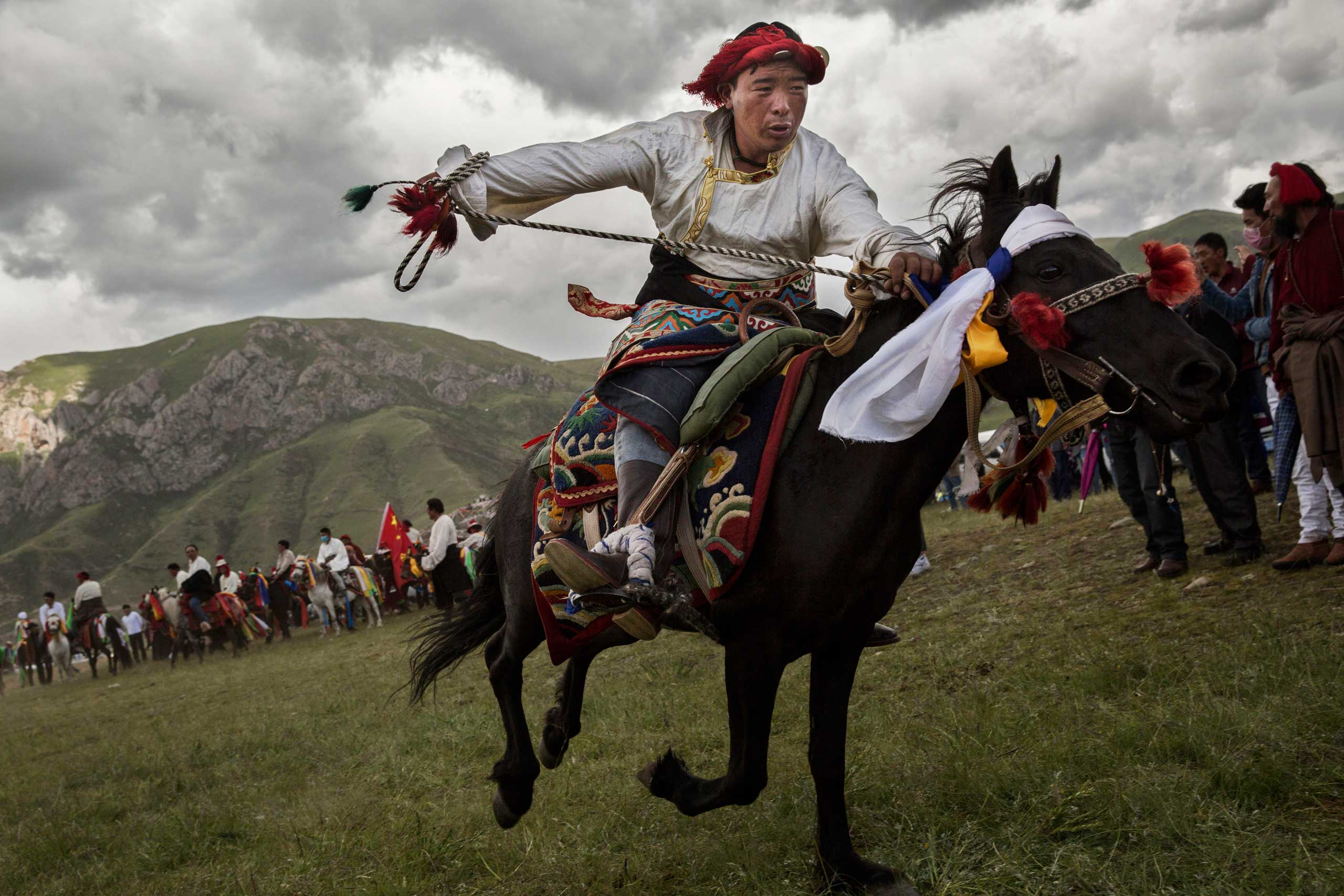 An ethnic Tibetan nomad performs skills during a riding competition at a local festival on the Tibetan Plateau in Yushu County, on July 26, 2015.