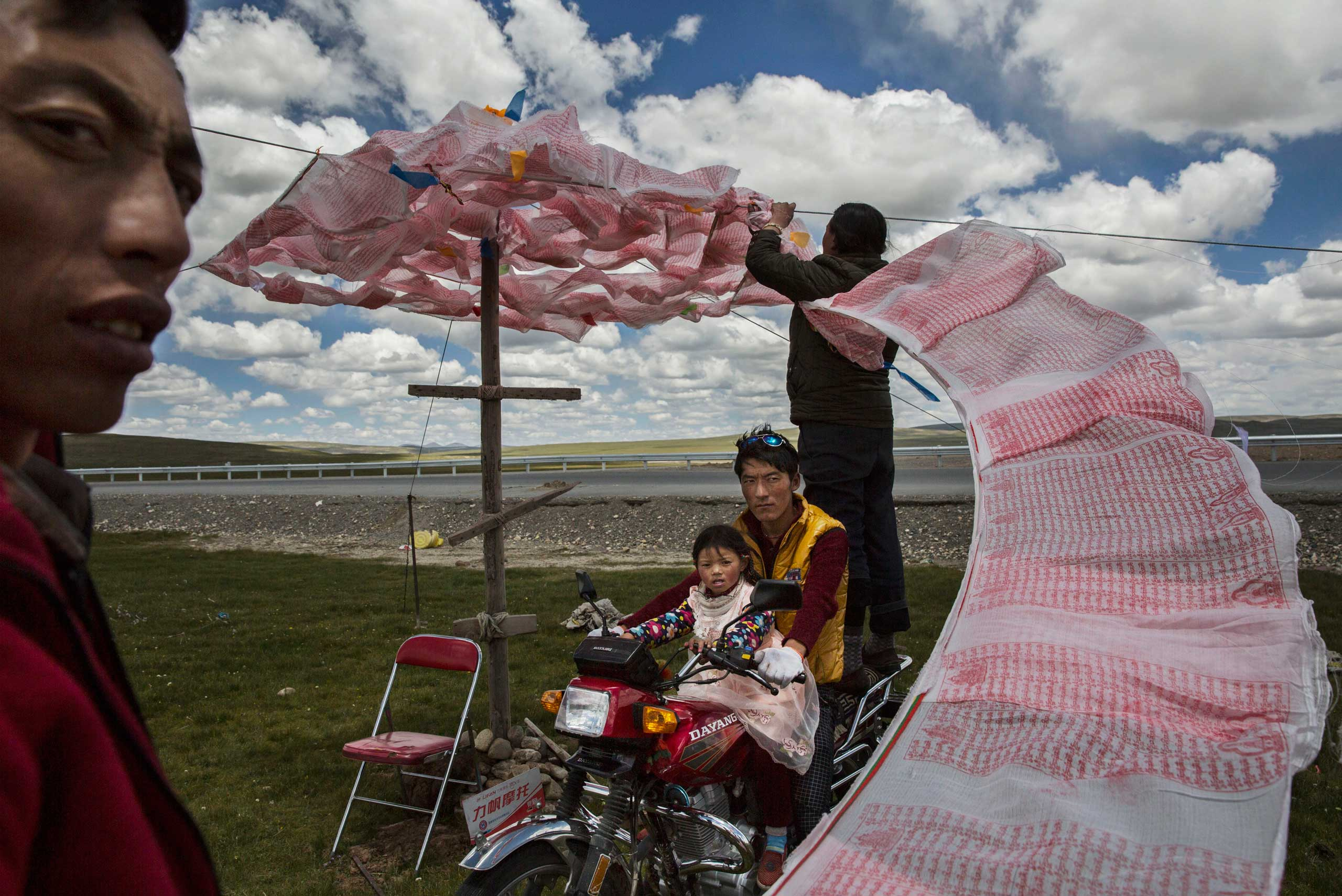 Tibetan nomads put up a string of Buddhist prayer flags near a government resettlement community on the Tibetan Plateau in Madou County, on July 24, 2015.