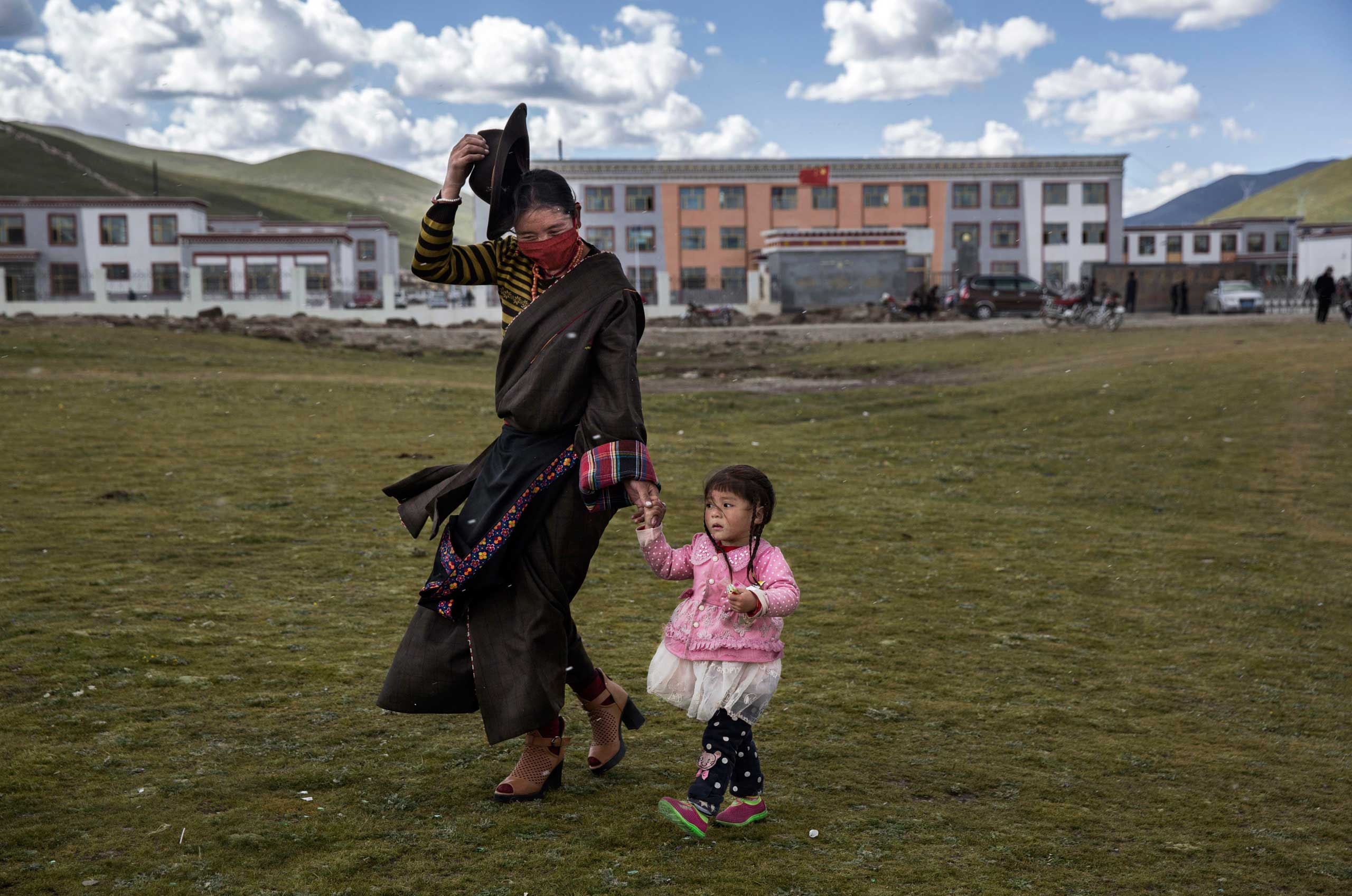 A Tibetan woman holds on to her hat in strong winds as she walks her daughter home from a Chinese government school in a resettlement community on the Tibetan Plateau in Yushu County, on July 23, 2015.