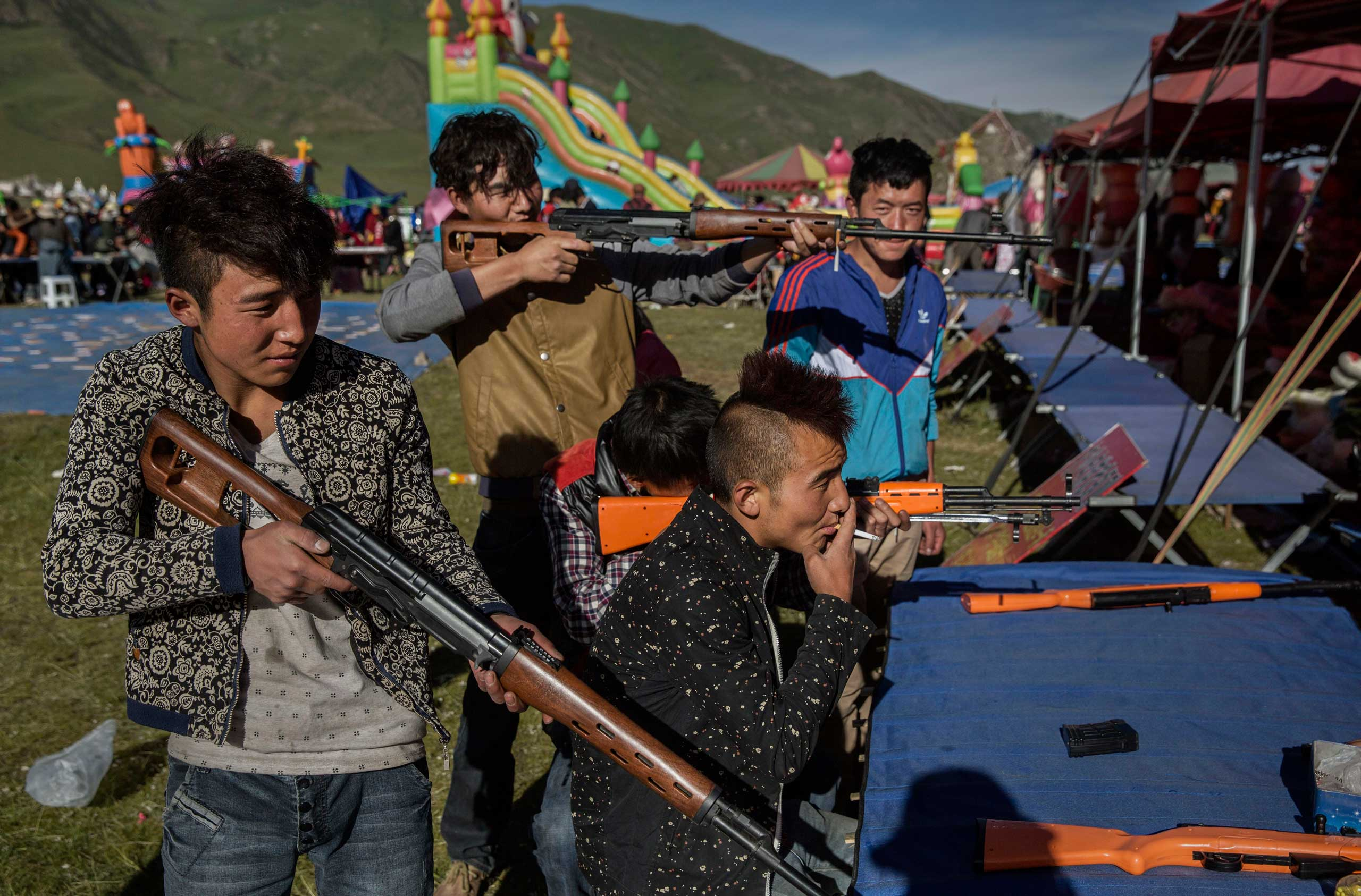 Tibetan youths hold air rifles as they play a game at a local festival on the Tibetan Plateau in Yushu County, on July 26, 2015.
