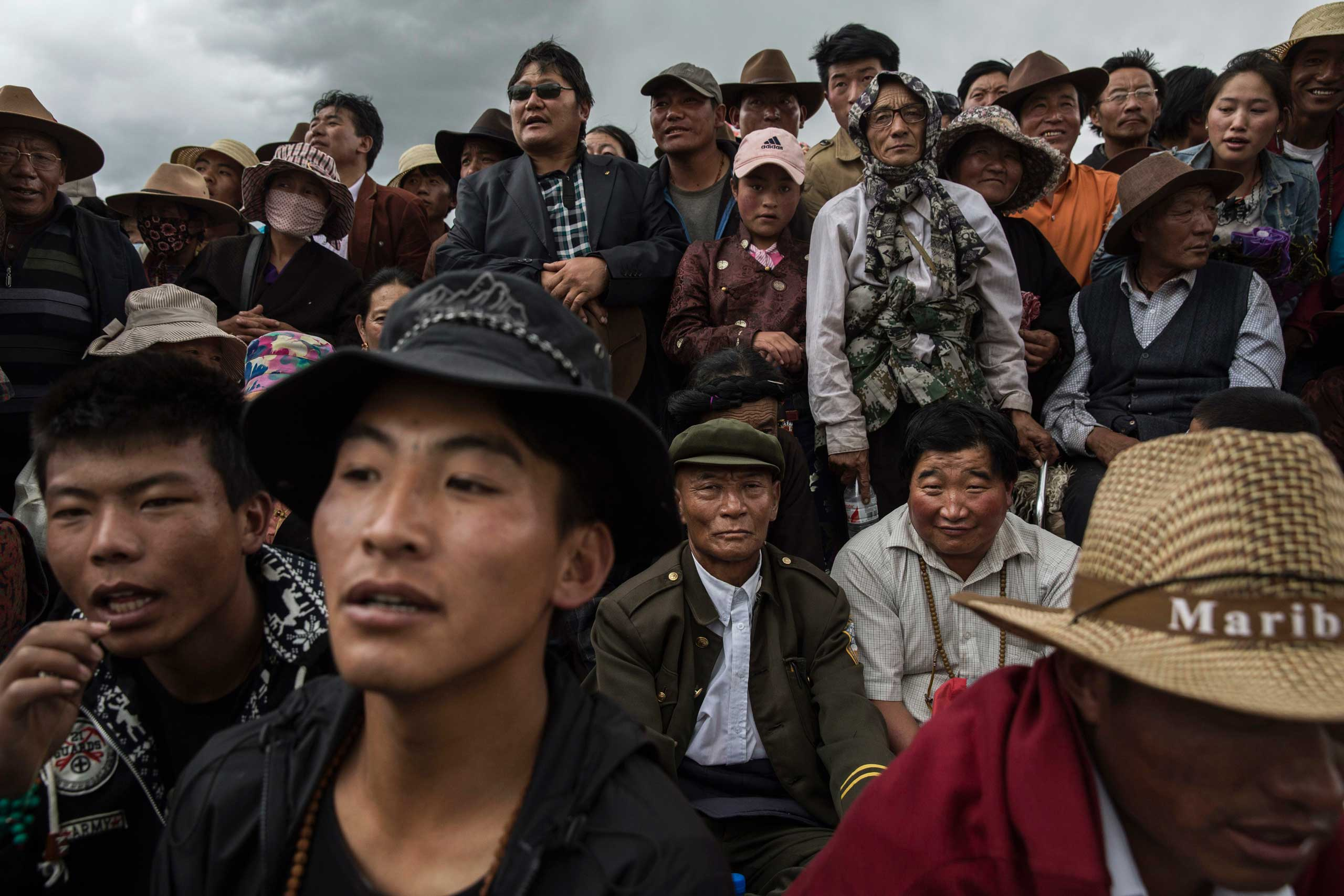 Tibetan watch as nomads perform skills during a riding competition at a local government sponsored festival on the Tibetan Plateau in Yushu County,  on July 26, 2015.