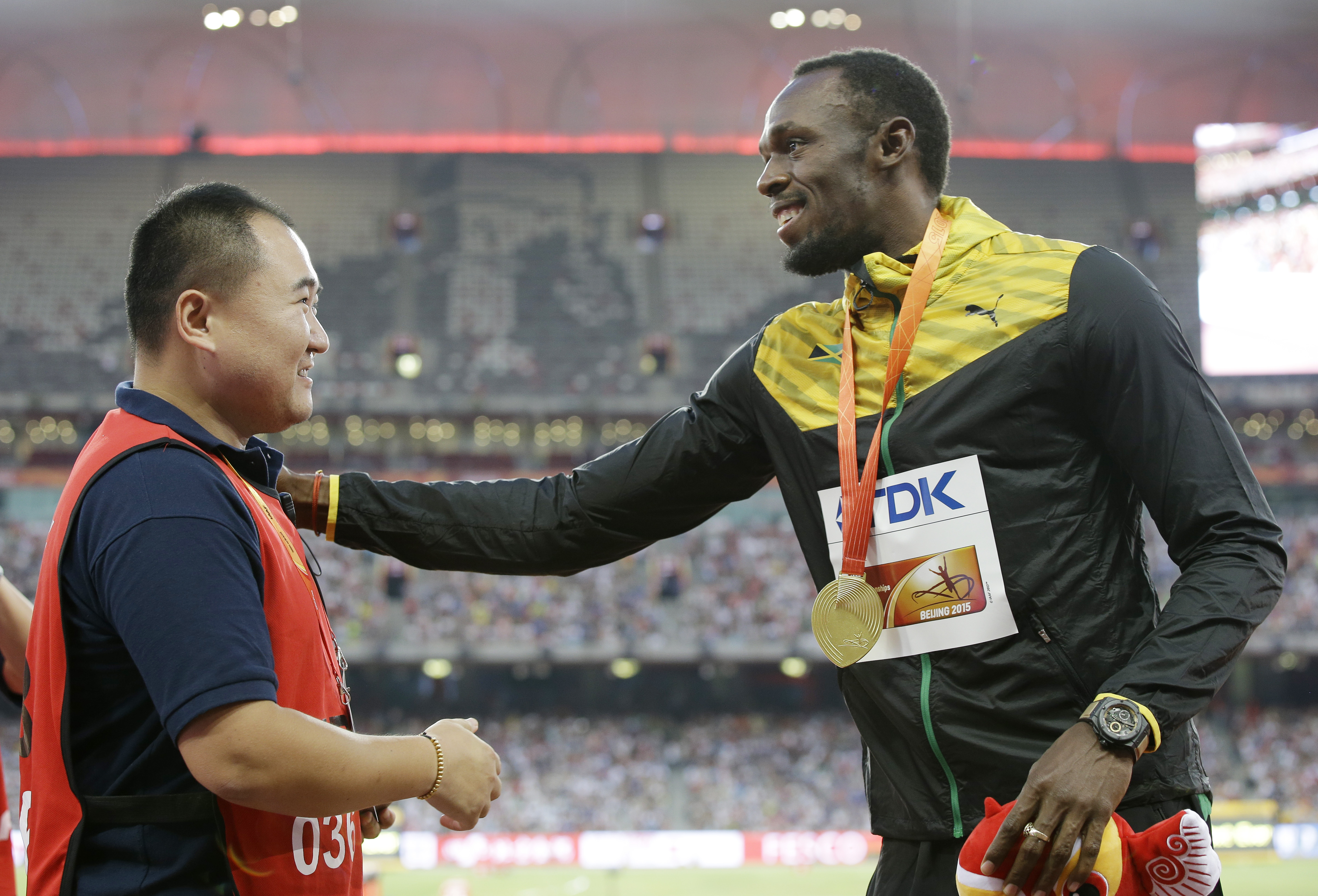 Jamaica's Usain Bolt, left, receives a gift from the cameraman who hit Bolt with a segway after the 200m final on Aug. 27.