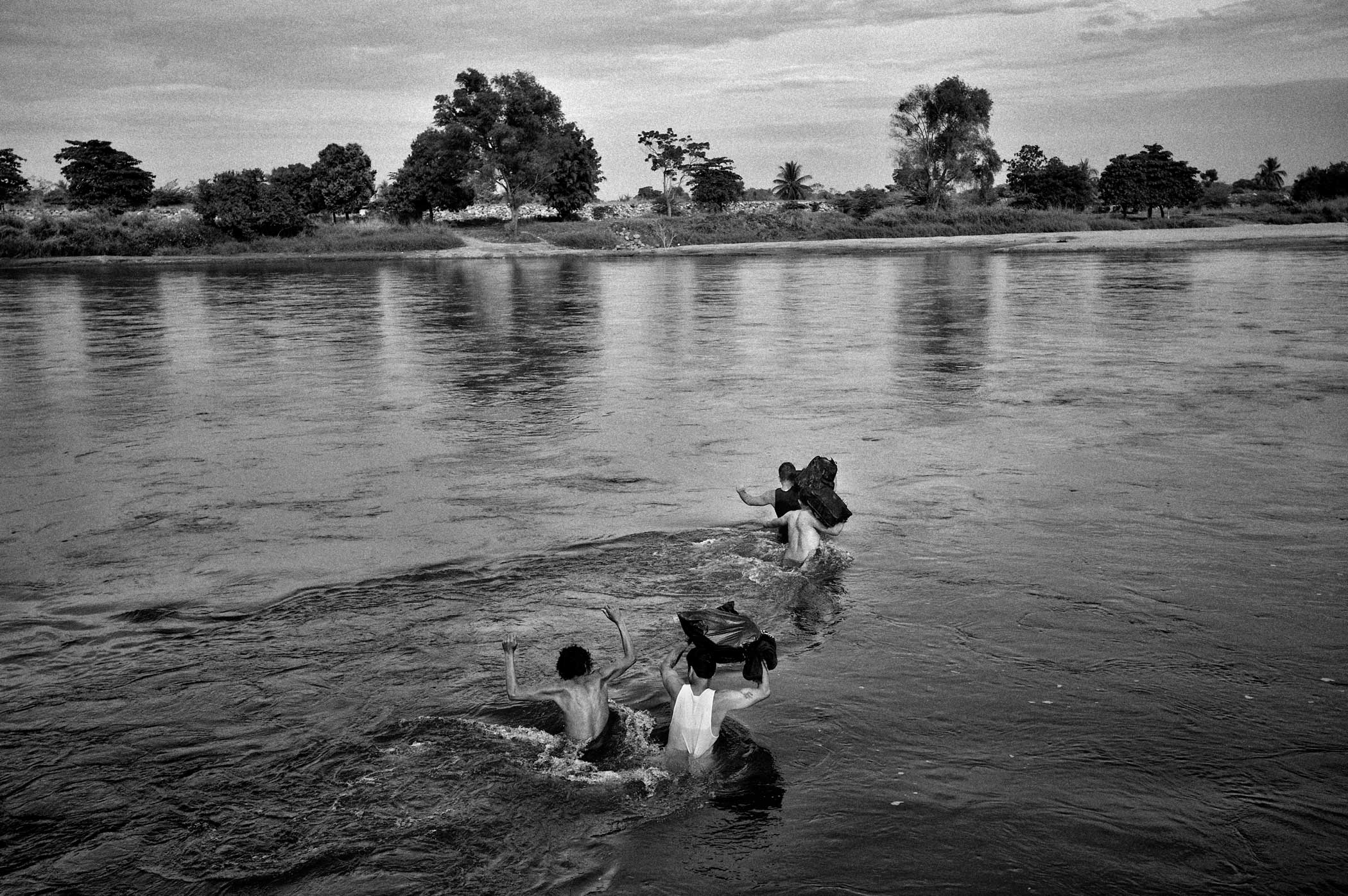 Wilmer Arias (38),in front, from Honduras is crossing the Suchiate river, the border between Guatemala and Mexico. Wilmer is on his way to Canada. He used to live there before he was deported, his two children still live there and he will try to visit them.