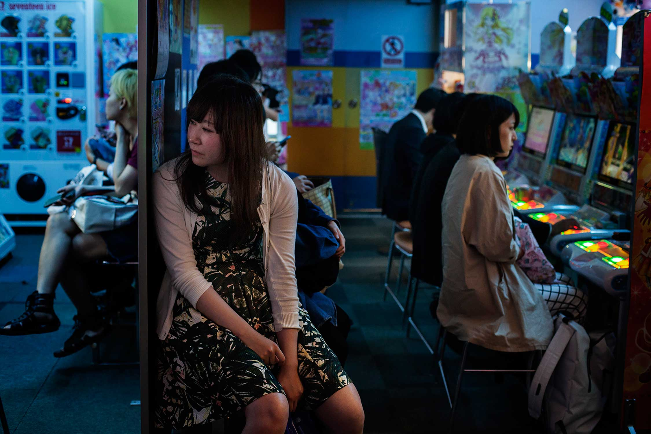 A women watches players in a Patchinko hall on a Friday night in Akihabara district, Tokyo.