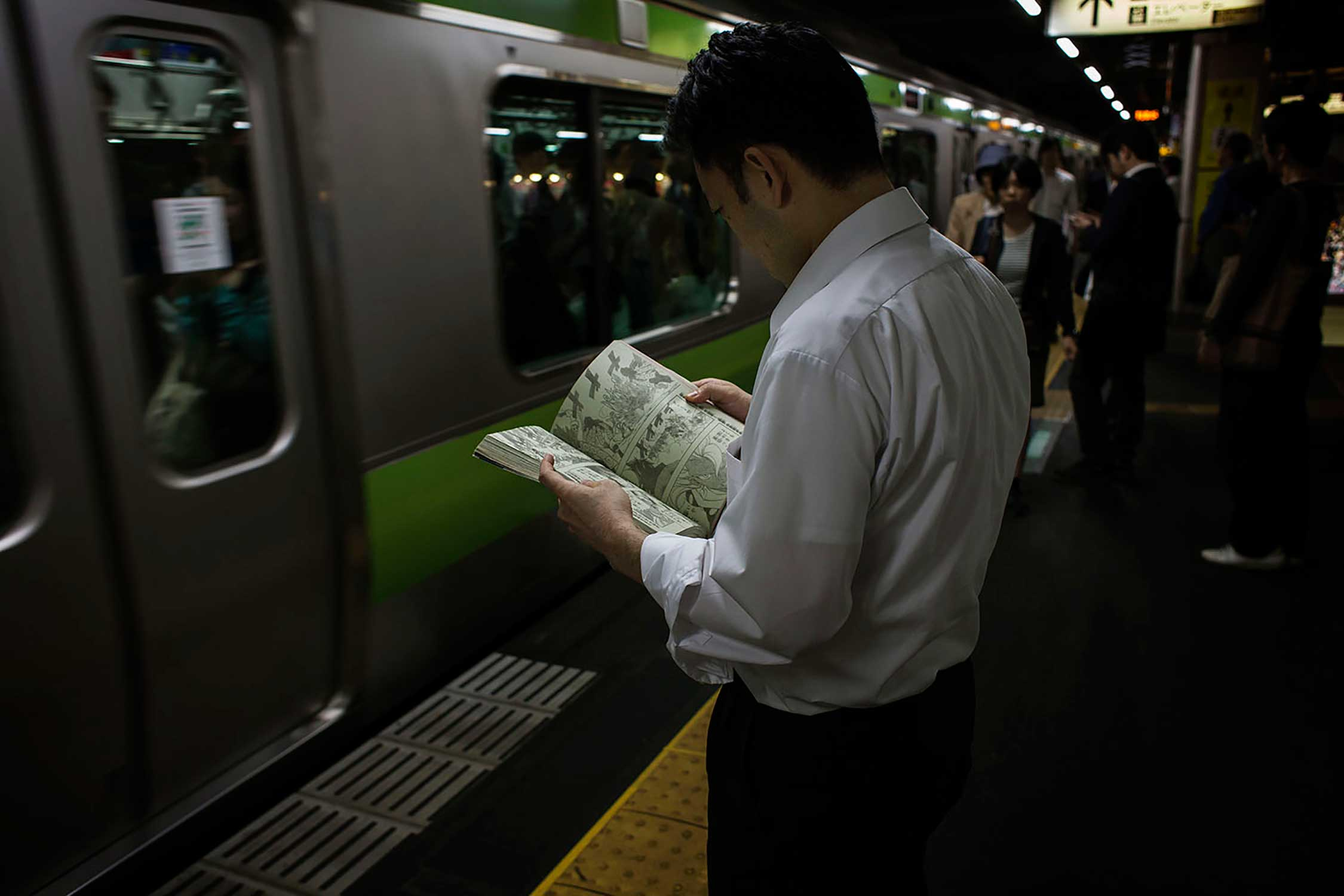A man reads a Manga magazine while he waits for the subway train after a day of work in Tokyo.