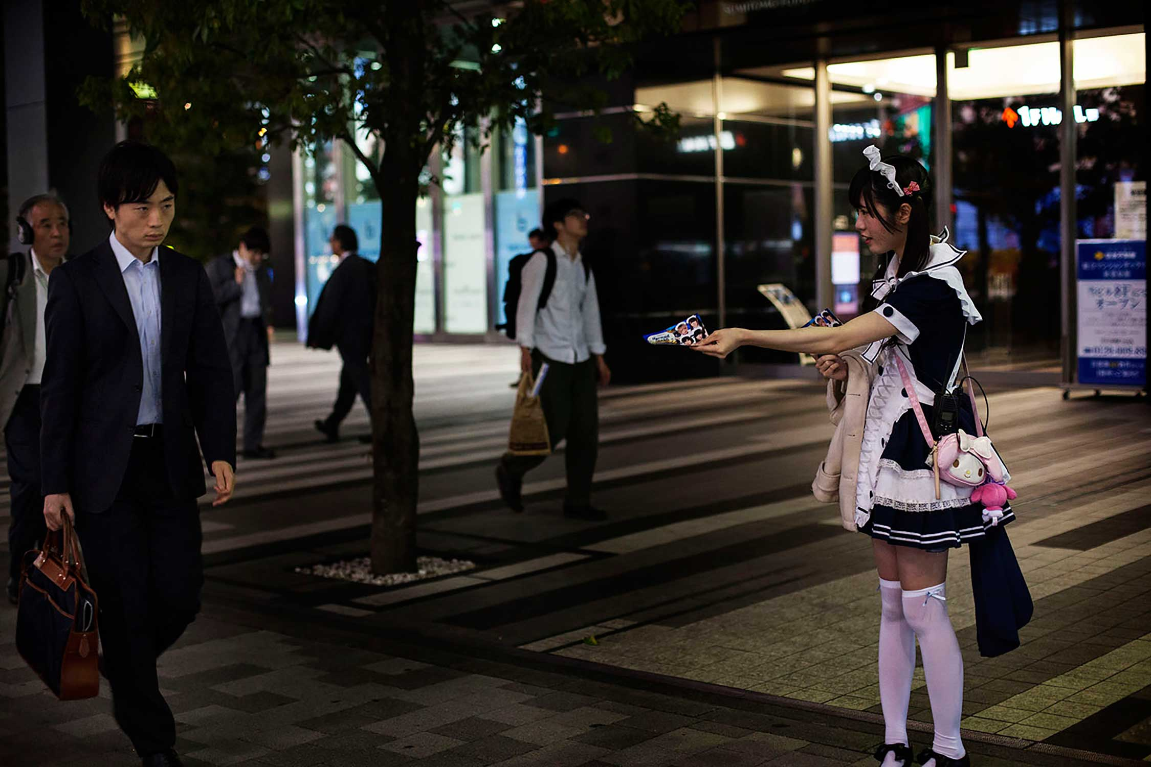 A waitress dressed as a cosplayer tries to hand out a flyer to a passer-by on a street in Akihabara, a district famous for its electronic shops and Otome cafés in Tokyo.