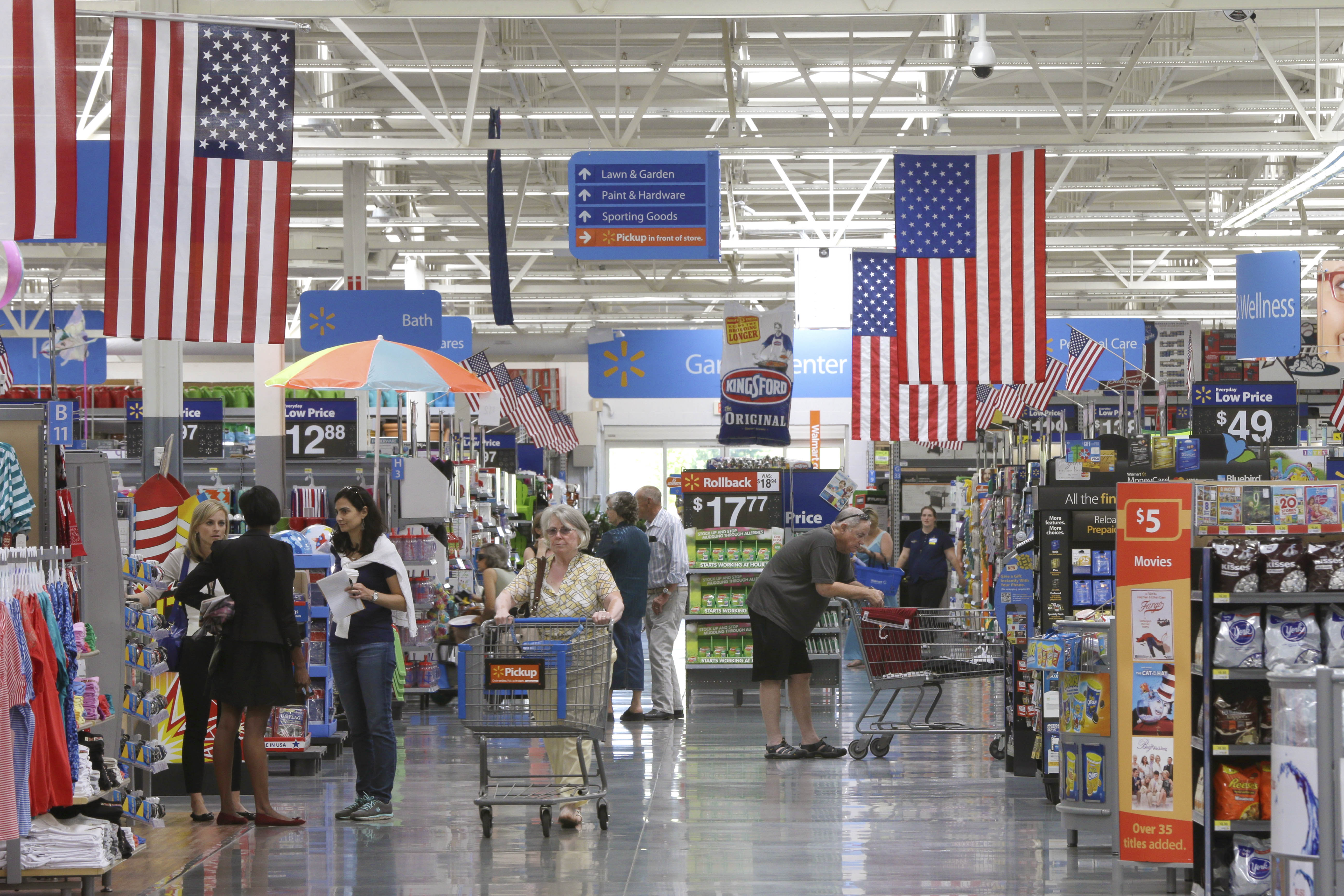 Customers shop on widened aisles at a Wal-Mart Supercenter store in Springdale, Ark., Thursday, June 4, 2015.
