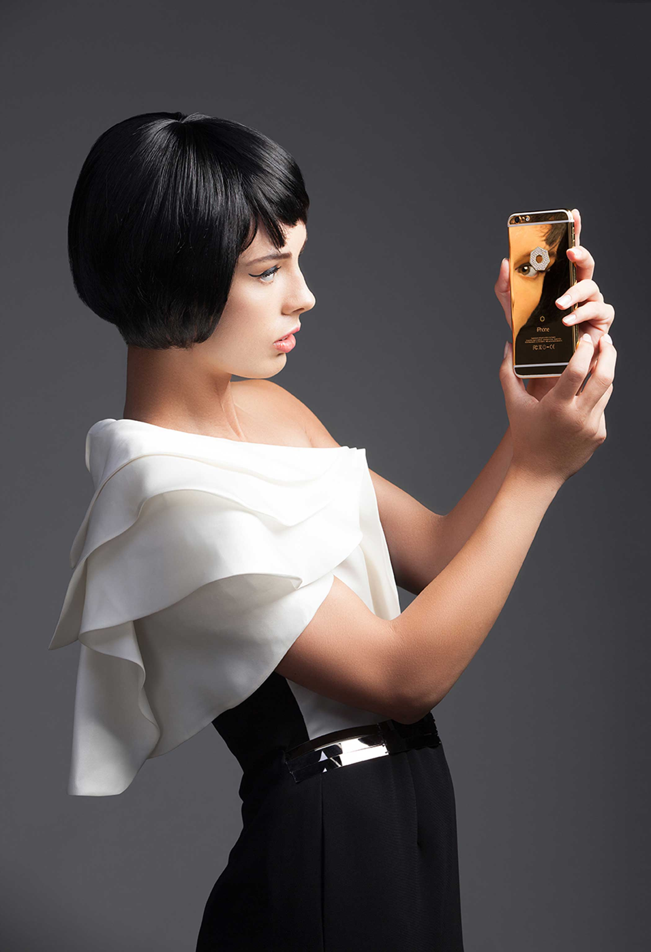 A model sees her own reflection in the Lux iPhone 6s Plus Diamonds Large in 24-karat yellow gold ($10,895).
