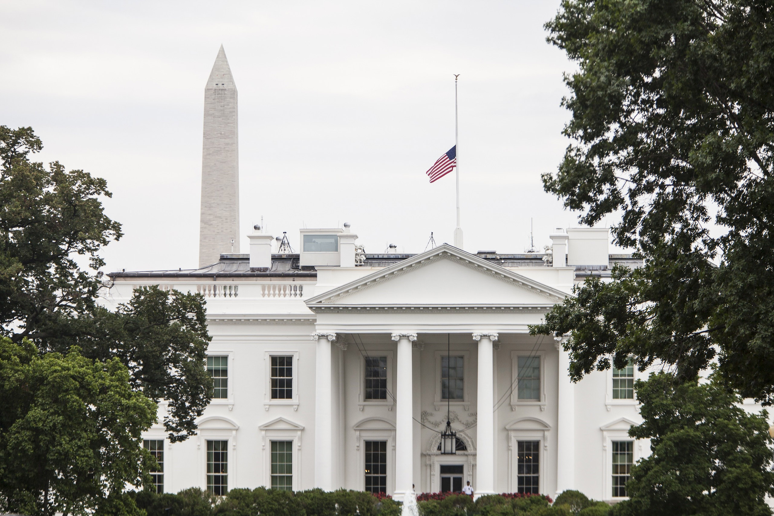 The American Flag flies above the White House after President Barack Obama ordered it lowered to half staff in honor of the four Marines and one Sailor killed in Chattanooga, TN in Washington,  on July 21, 2015.