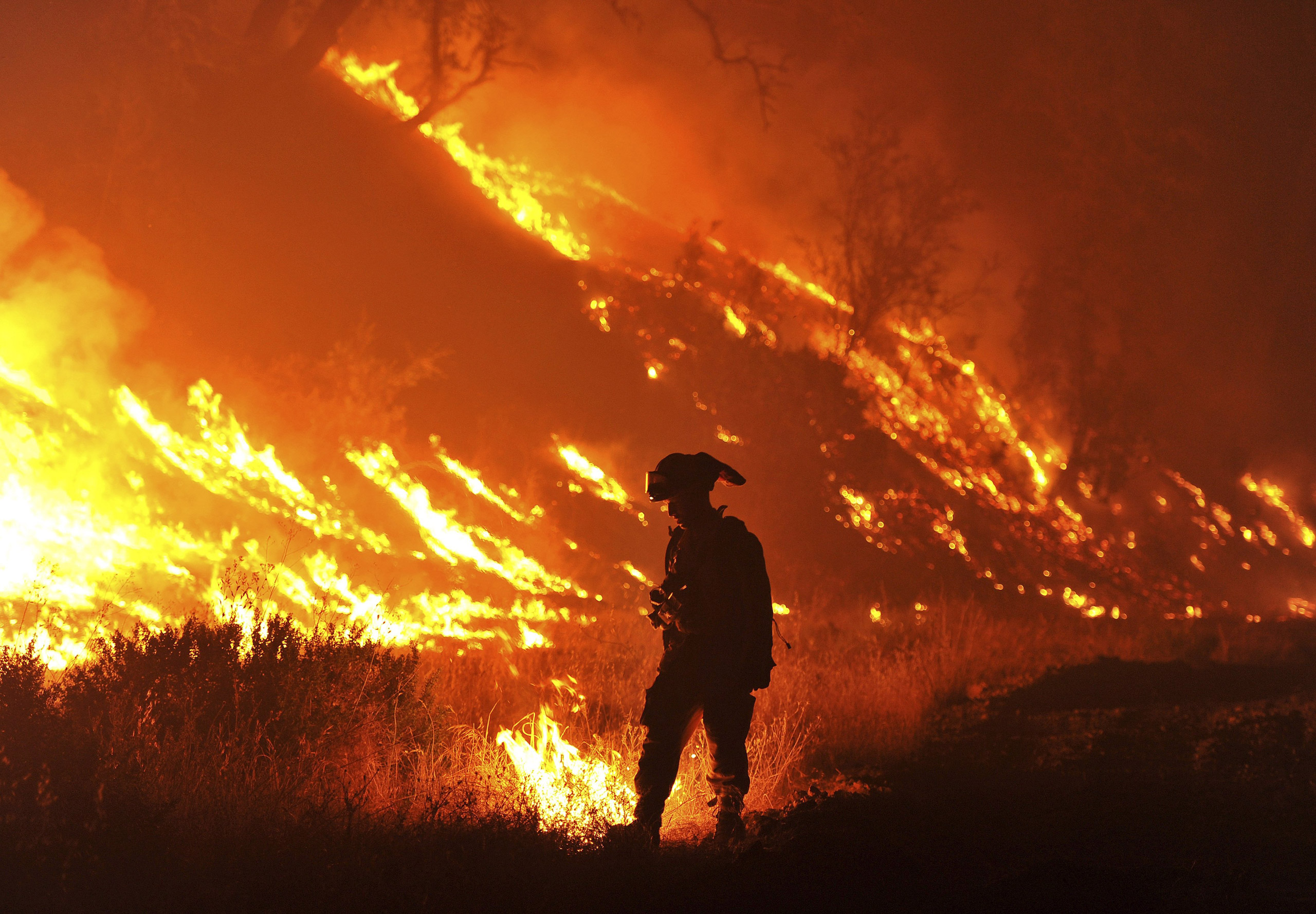 CalFire firefighter Bo Santiago lights a backfire as the Rocky fire burns near Clearlake, Calif., on Aug. 3, 2015.