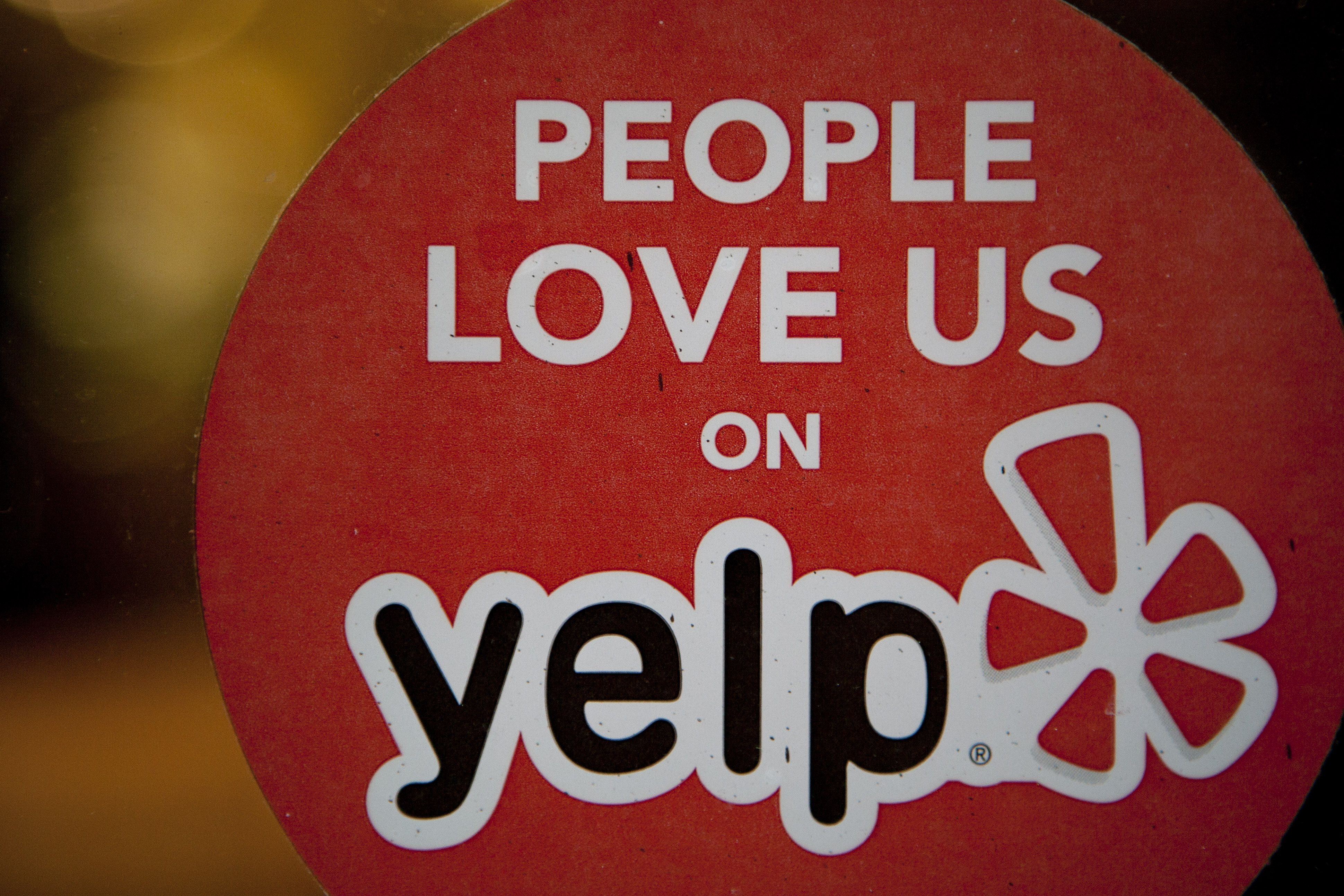 The Yelp logo is displayed in the window of a restaurant in New York on March 1, 2012.