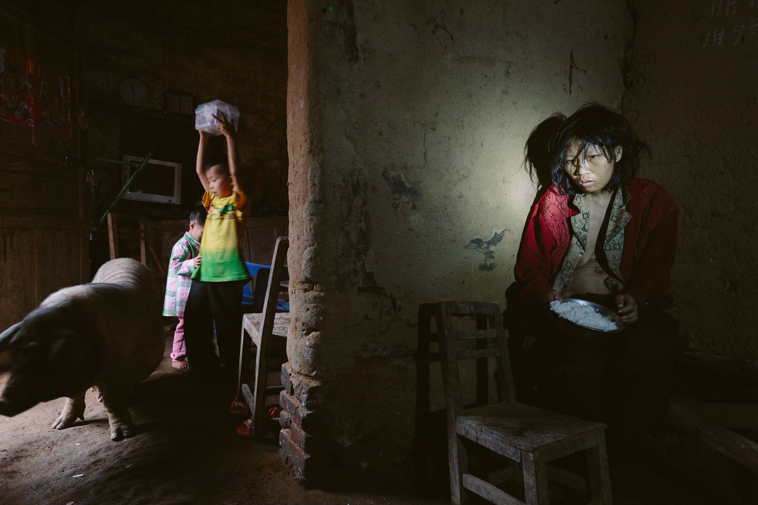 The Guardian: At Home With Mental Illness                               Nine-year-old Tong Xiao and his younger sister Ling Xiao are protecting their food box from a pig. Their mother, Tongyimg Liu, is having her dinner in the corner. Maoming, China.