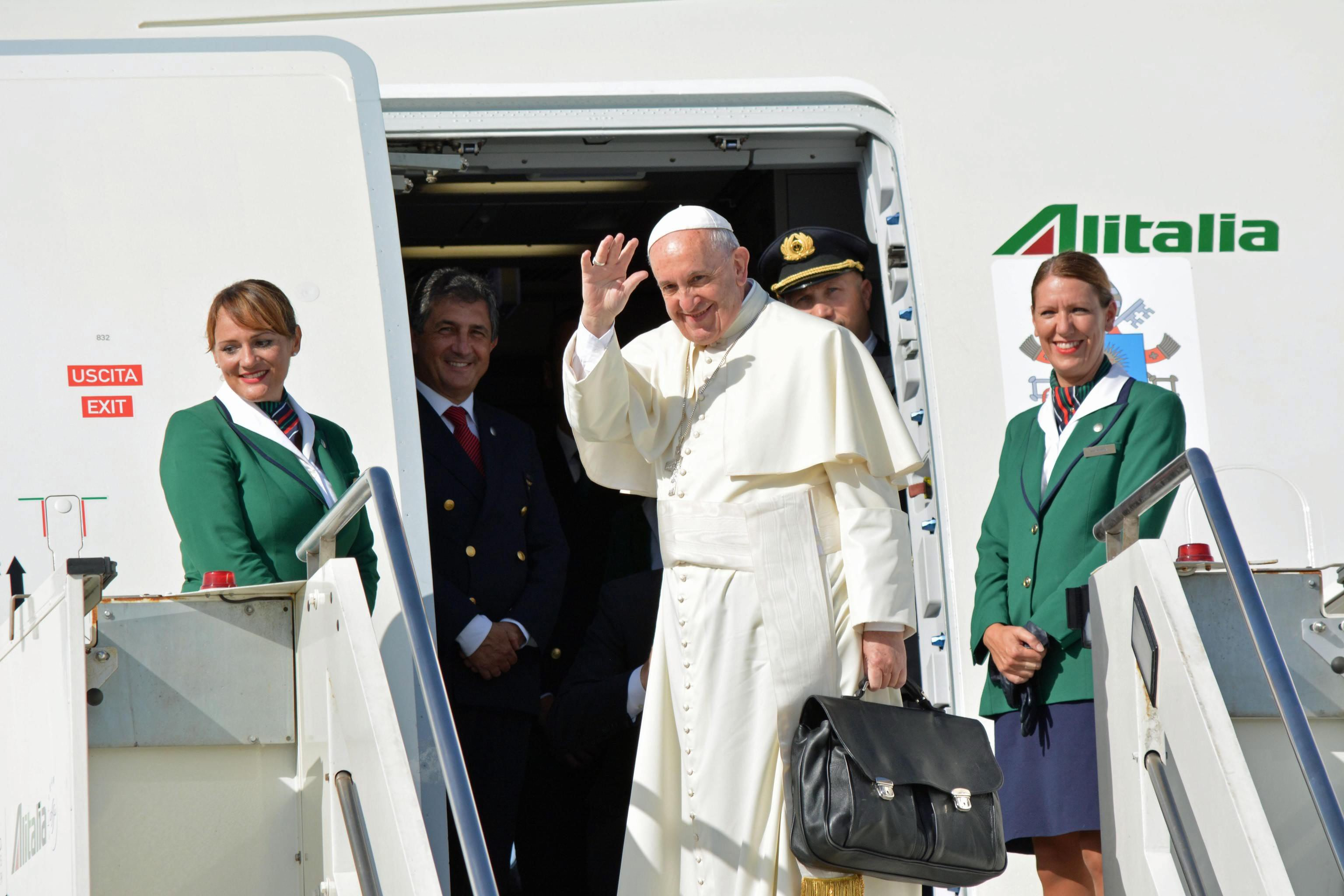 Pope Francis waves to reporters at Fiumicino international airport as he boards his flight to Havana, Cuba, from Rome, on Sept. 19, 2015.