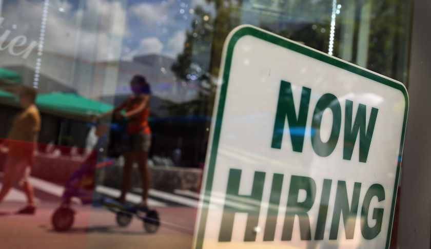 A 'Now Hiring' sign is seen in a storefront window in Miami Beach, Fla.