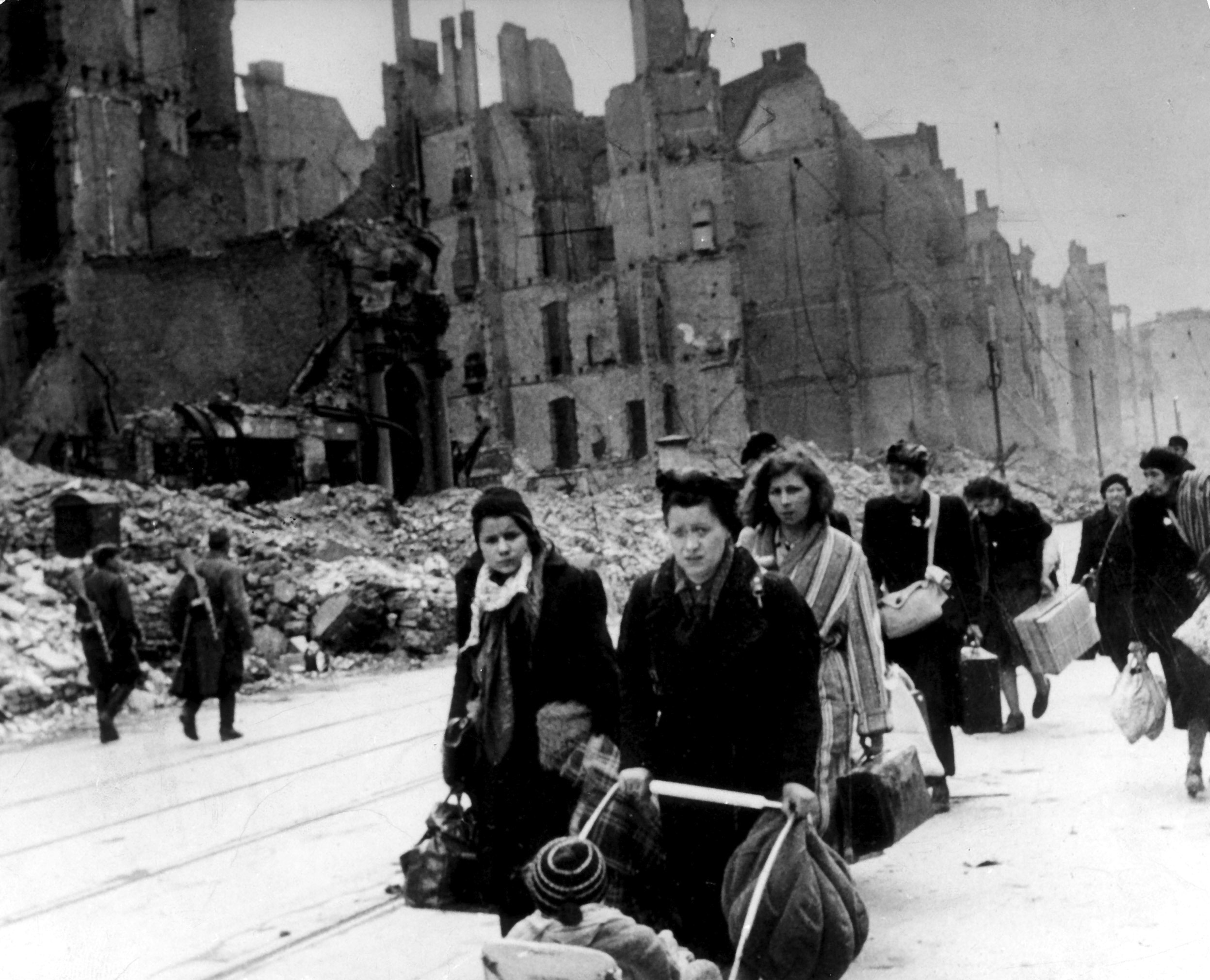 A stream of refugees and people who have been bombed out of their homes moving through destroyed streets in Germany in 1945, after end of war. On the left, two Soviet soldiers can be seen patrolling.