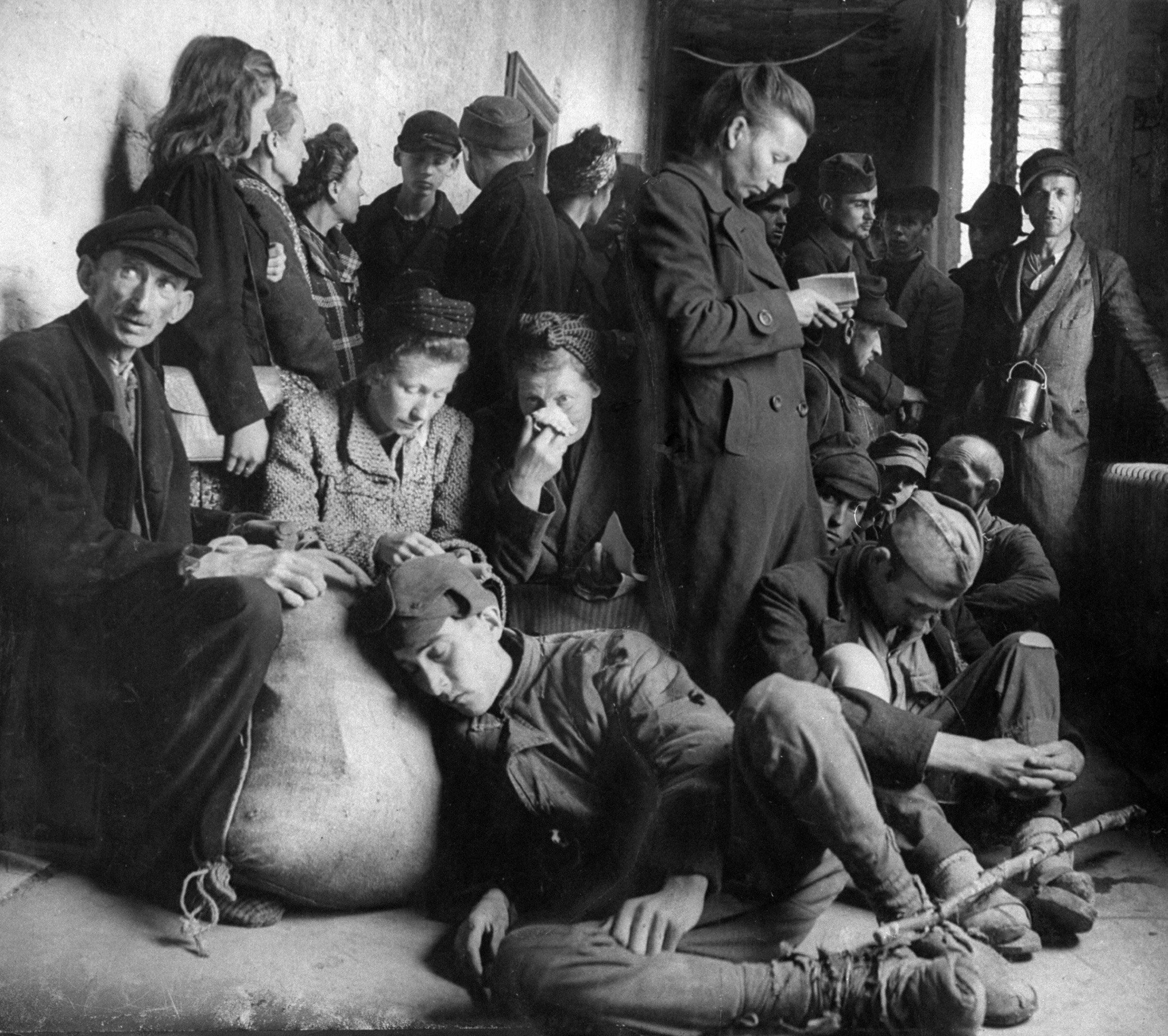 Exhausted, homeless German refugees huddled in a city municipal building seeking shelter. 1945.