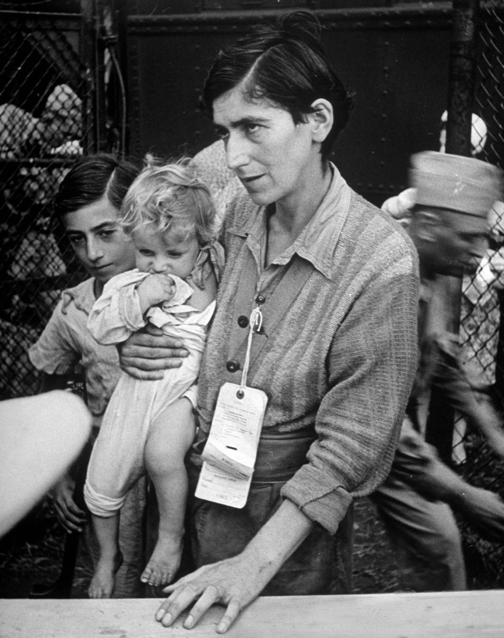 Swiss Jew Eva Bass, formerly a nightclub singer in Paris, entering refugee camp at Fort Ontario, with her children Yolanda and Joachim, whom she carried on a 60-km trek through the fighting lines to reach the American transport ship Henry Gibbins. 1944.